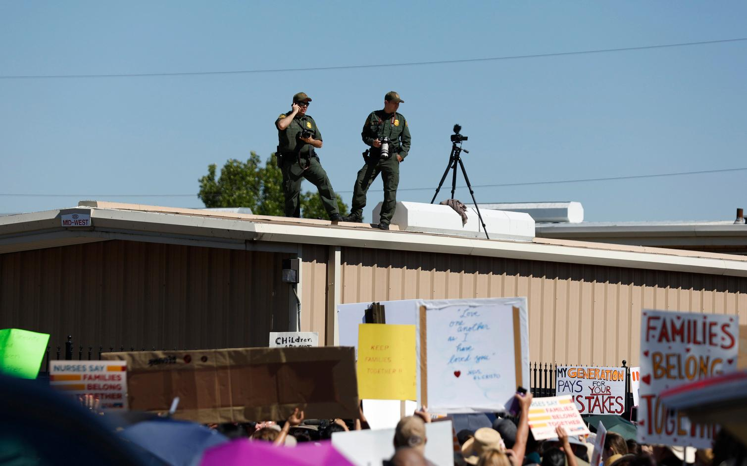 U.S. Border Patrol agents watch as they take photos and video of the crowd protesting outside the U.S. Immigration and Customs Enforcement processing center in El Paso, Texas, Tuesday, June 19, 2018. (Ivan Pierre Aguirre/The San Antonio Express-News via AP)