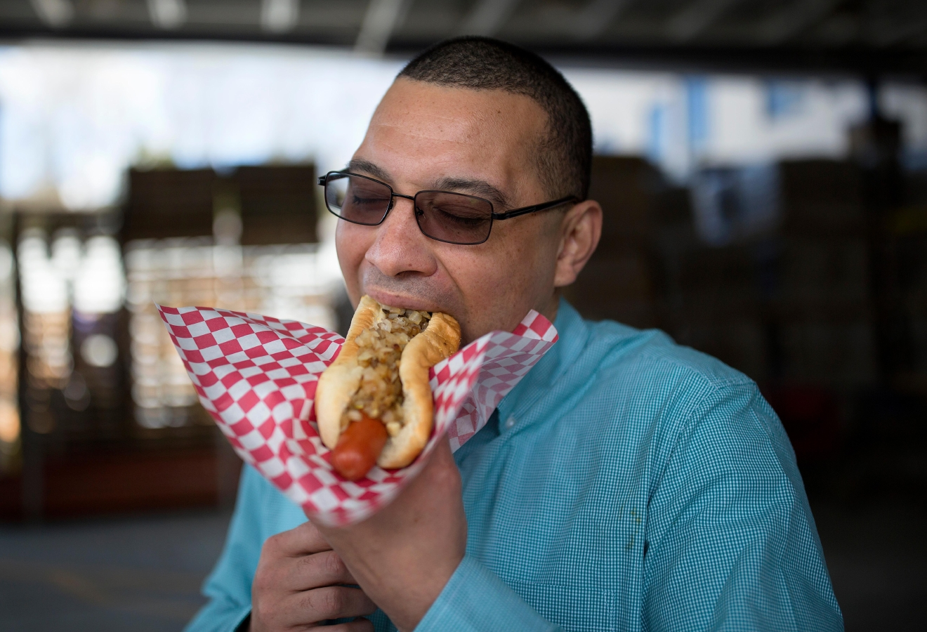 Alan Wedge, a regular of Rain City Hot Dogs, eats his favorite hotlink with Jamaican sauce, outside the Lowe's on Rainier Ave. (Sy Bean / Seattle Refined)