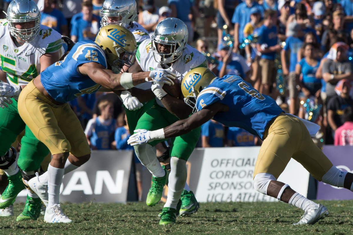 Oregon running back Royce Freeman (#21) runs into UCLA defenders Kenny Young (#42) and Adarius Pickett (#6). The Oregon Ducks fell to the UCLA Bruins 14-31 after being shut out during the second half at the Rose Bowl Stadium in Pasadena, California.  This marks the third consecutive loss for the Ducks, dropping their record to 4-4 on the season.  Photo by Austin Hicks, Oregon News Lab