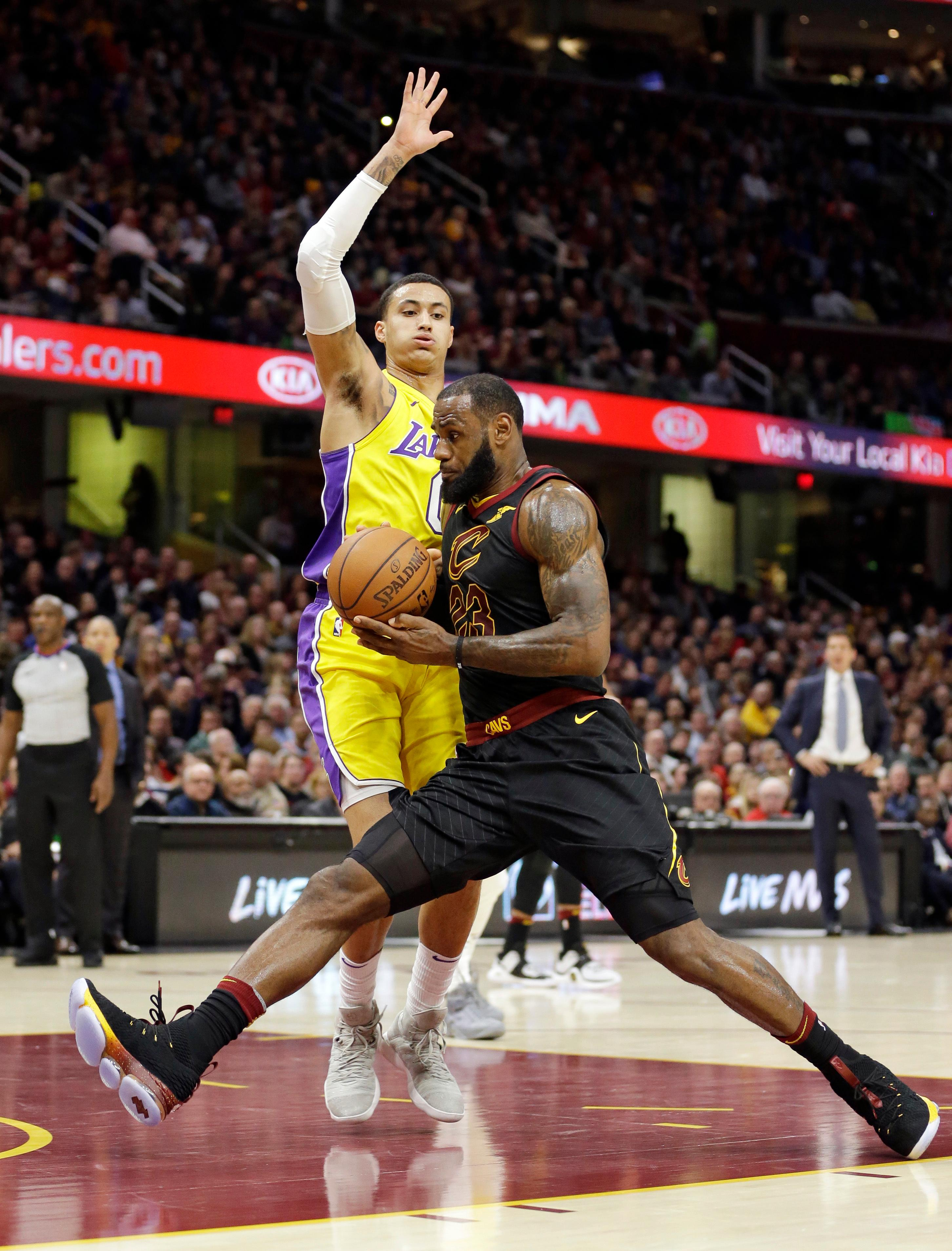 Cleveland Cavaliers' LeBron James, right, drives past Los Angeles Lakers' Kyle Kuzma in the first half of an NBA basketball game, Thursday, Dec. 14, 2017, in Cleveland. (AP Photo/Tony Dejak)