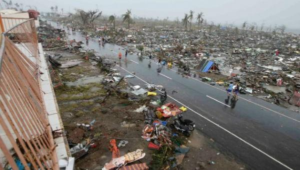 People walk past the devastation caused by Typhoon Haiyan in Tacloban.
