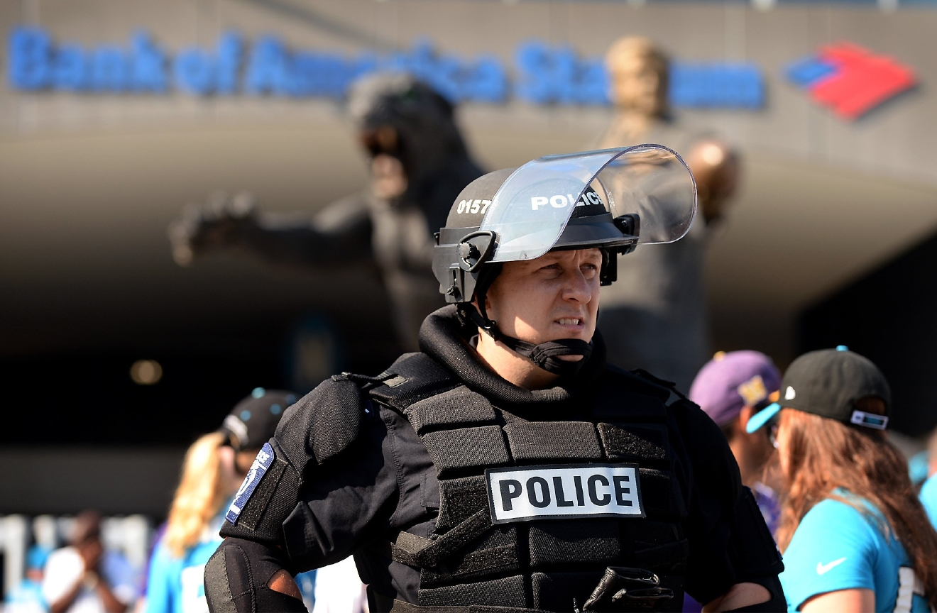 A Charlotte-Mecklenburg police officer in riot gear watches foot traffic pass an entrance area at Bank of America Stadium, where people were protesting, prior to an NFL football game between the Minnesota Vikings and the Carolina Panthers in Charlotte, N.C., Sunday, Sept. 25, 2016. When the national anthem was played, the protesters all dropped to one knee as many NFL players have been doing for weeks to call attention to issues, including police shootings. (Jeff Siner/The Charlotte Observer via AP)