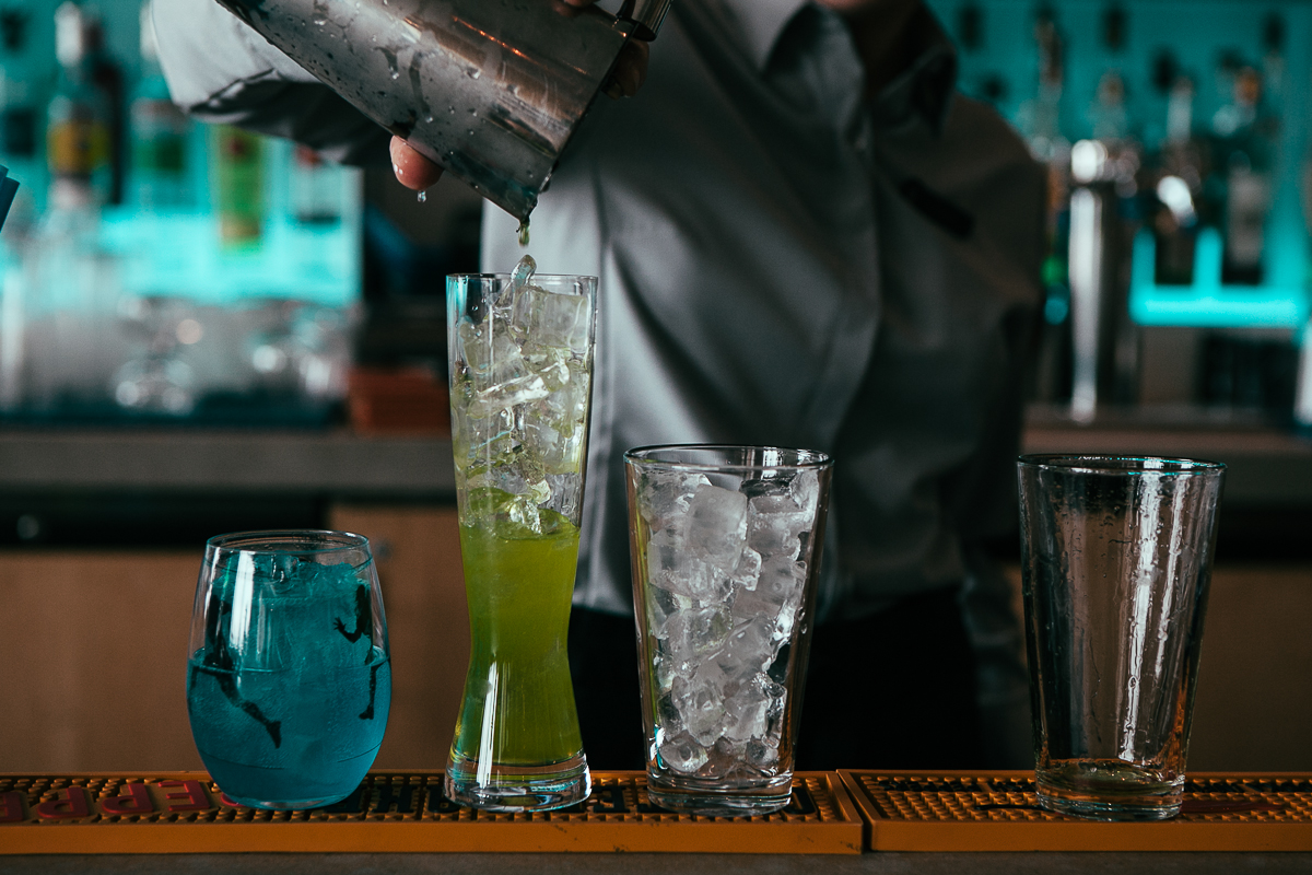 "Art Restaurant shows their Blue Pride with two unique cocktails: the ""Super Bowl Sling,"" which offers warship rum infused with blue skittles, Benedictine and orange bitters, and the ""12th Man,"" a bright-action green-colored cocktail with celestial reposado infused with green skittles, Cointreau, house sour mix and a mini 12th man flag garnish to top it off. (Image: Joshua Lewis / Seattle Refined)"