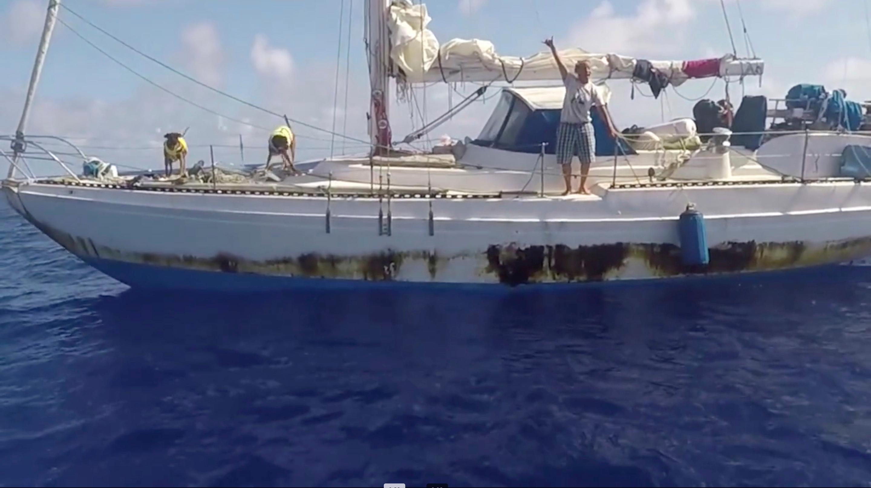 In this Wednesday, Oct. 25, 2017 still image taken from video provided by the U.S. Navy, Jennifer Appel, of Honolulu, holds up a shaka sign as rescuers approach her crippled sailboat, the Sea Nymph. (U.S. Navy via AP)<p></p>