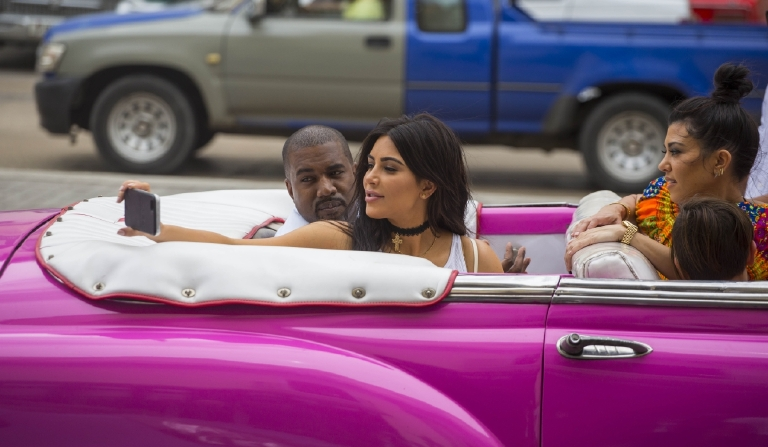 CORRRECTS NAME OF KANYE WEST - American reality-show star Kim Kardashian takes a selfie as she rides on a classic car next to her husband, rap superstar Kanye West and her sister Kourtney Mary Kardashian in Havana, Cuba, Wednesday, May 4, 2016. West, the Kardashians and members of her reality-show-star family have become the latest celebrities to visit Havana. They visited HavanaÂ?s Museum of Rum Wednesday, stepping out of a hot-pink antique American convertible as they snapped selfies and were recorded by a television crew following them around.(AP Photo/Desmond Boylan)