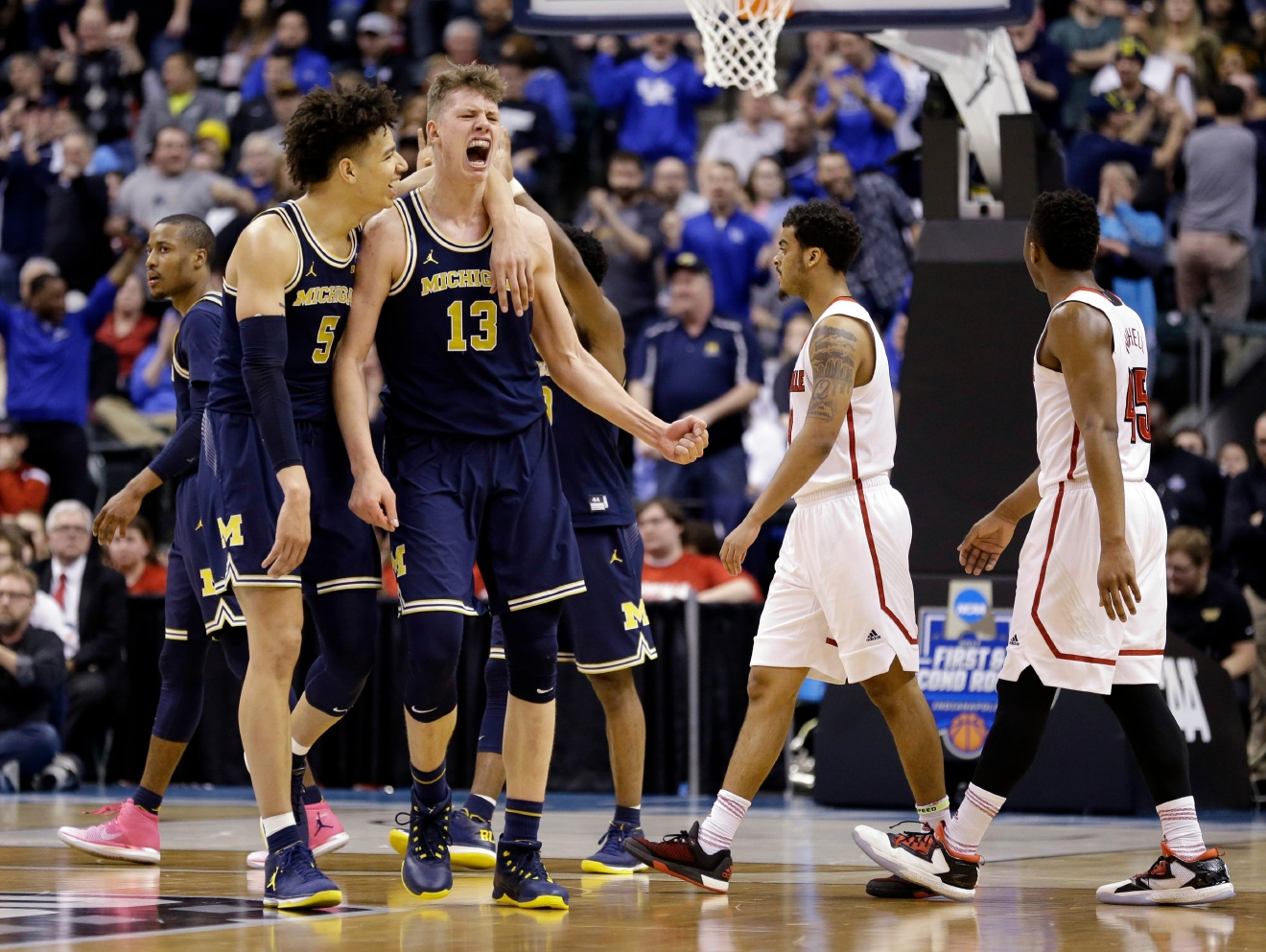 Michigan forwards D.J. Wilson (5) and Moritz Wagner (13) celebrates during the second half of a second-round game against Louisville in the men?s NCAA college basketball tournament in Indianapolis, Sunday, March 19, 2017. Michigan defeated Louisville 73-69. (AP Photo/Michael Conroy)