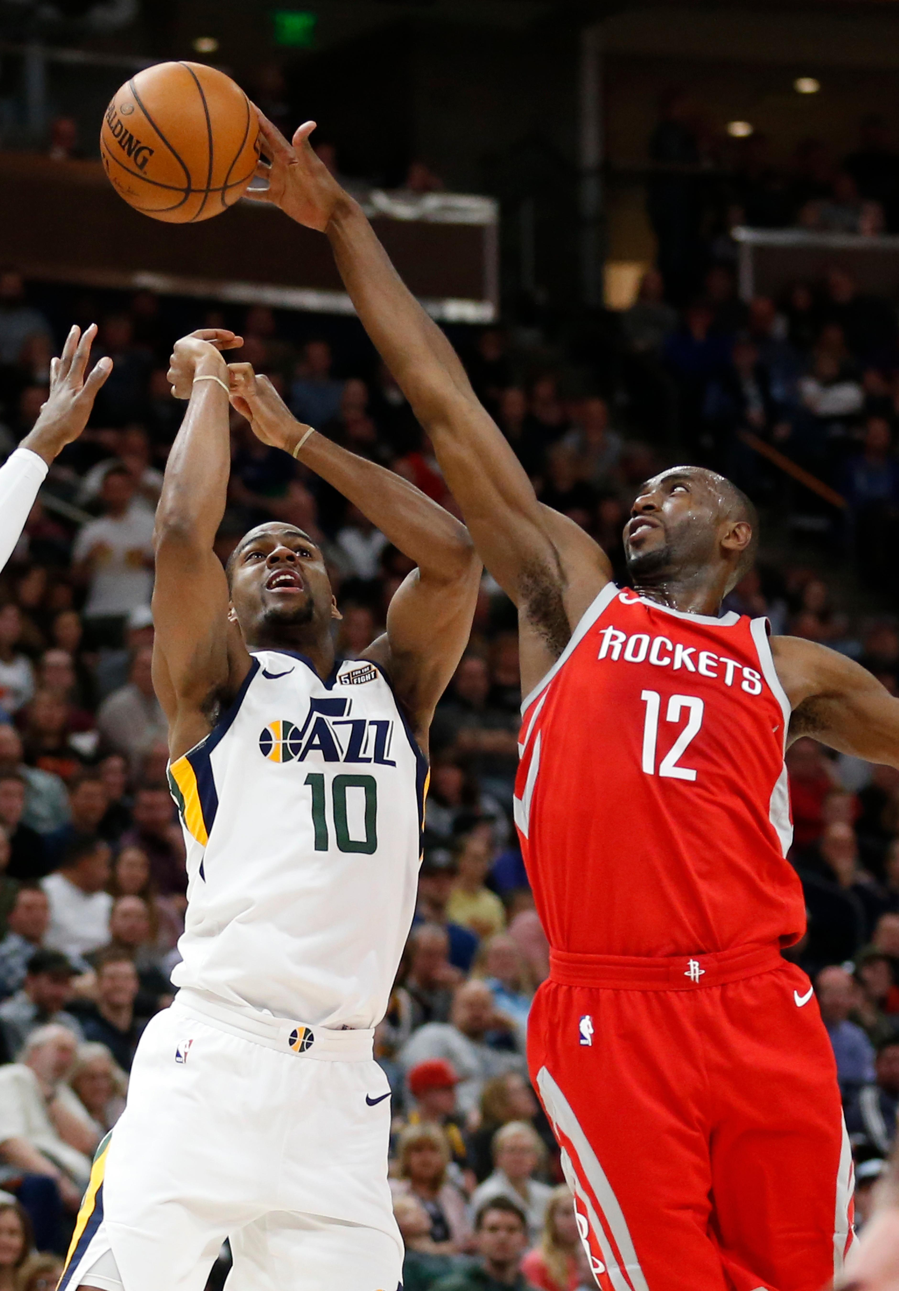 Houston Rockets forward Luc Mbah a Moute (12) blocks a shot by Utah Jazz guard Alec Burks (10) in the second half during an NBA basketball game Monday, Feb. 26, 2018, in Salt Lake City. (AP Photo/Rick Bowmer)