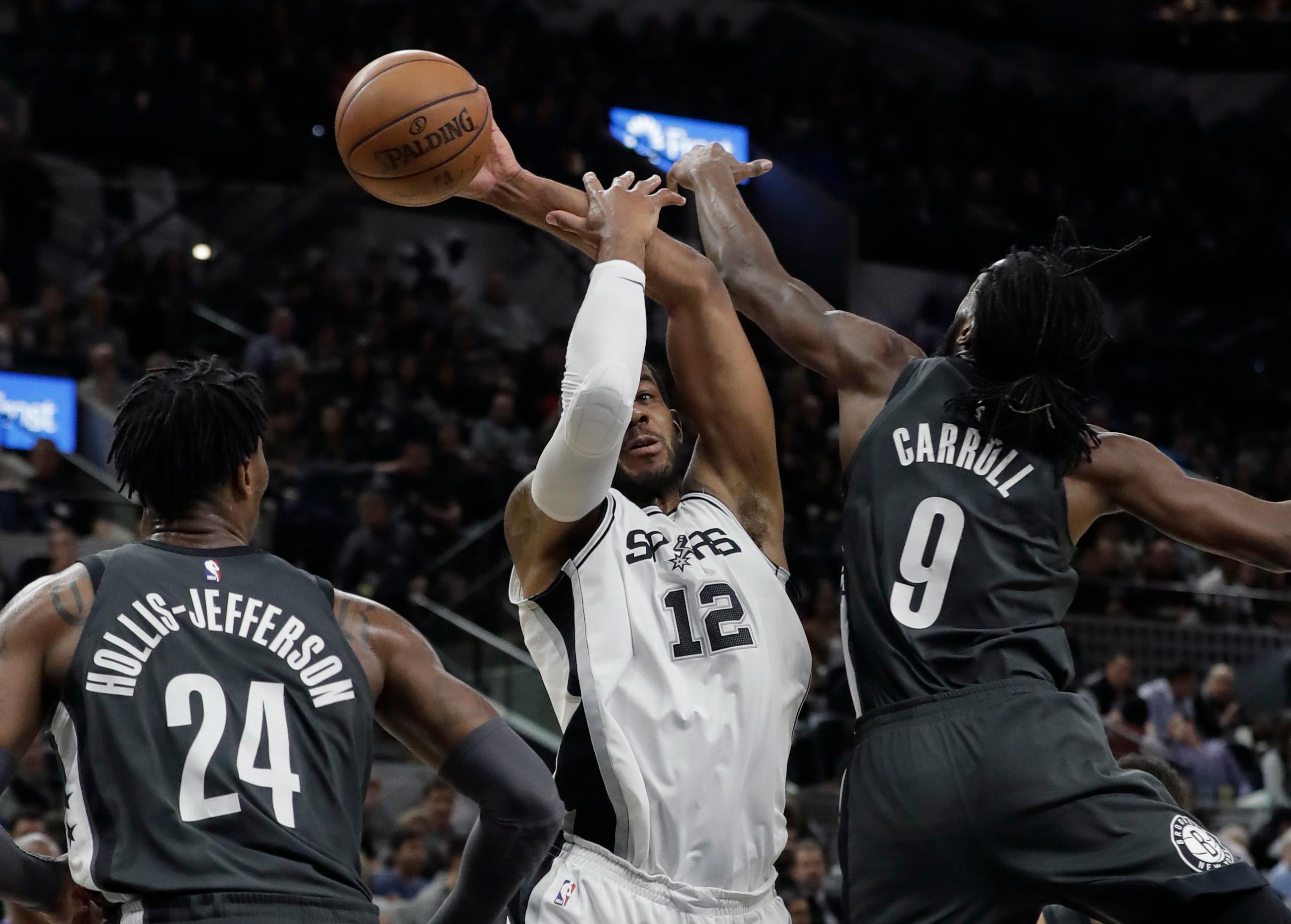 San Antonio Spurs forward LaMarcus Aldridge (12) is pressured by Brooklyn Nets forward DeMarre Carroll (9) as he tries to score during the first half of an NBA basketball game, Tuesday, Dec. 26, 2017, in San Antonio. (AP Photo/Eric Gay)