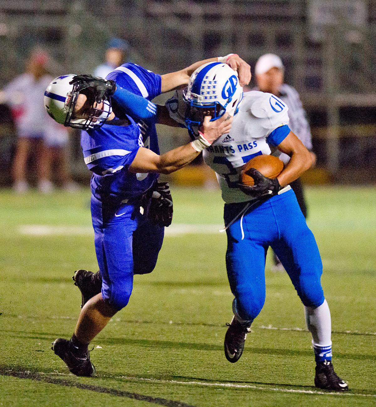 The South Axemen defender draws a face mask infraction on the Grants Pass Cavemen running back Adam Joham (#25). Grants Pass defeated South 13-6 at South's homecoming game. Photo by Dan Morrison, Oregon News Lab