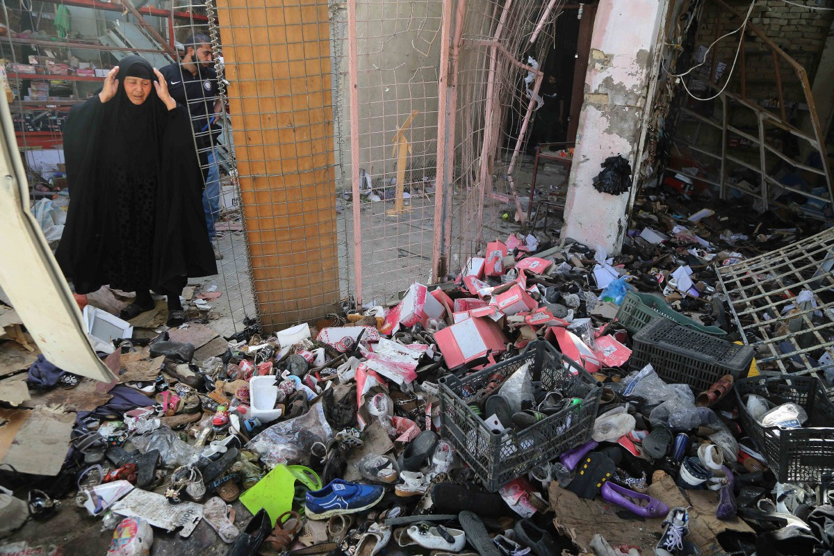An Iraqi woman inspects the aftermath of a suicide car bombing at a busy market in Khan Bani Saad in the Diyala province, about 20 miles (30 kilometers) northeast of Baghdad, Iraq, Saturday, July 18, 2015. A suicide car bombing in Iraq's eastern Diyala province killed at least 80 people gathered at a marketplace to mark the end of the holy month of Ramadan on Friday. (AP Photo/Karim Kadim)