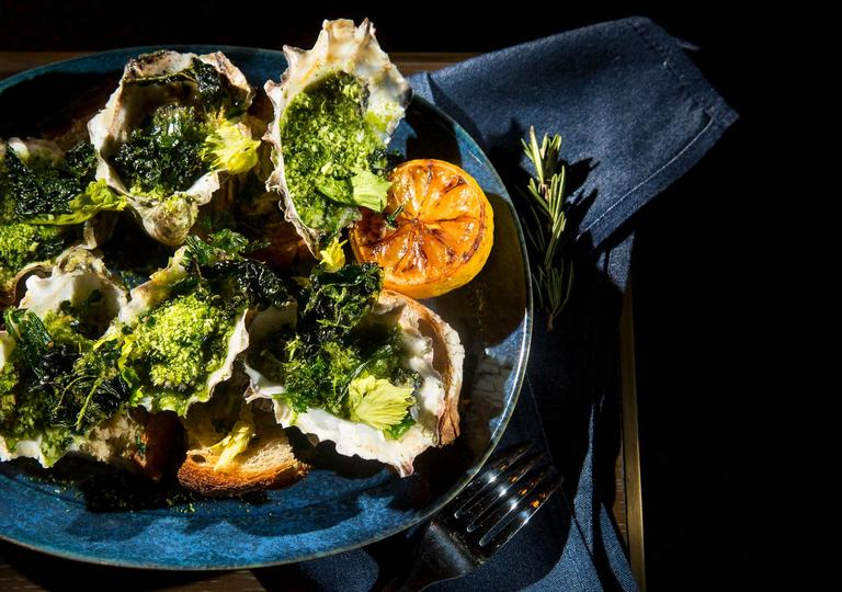 The Grilled Oysters, presented by executive chef David Nichols, consisting of garlic butter, parsley, and grilled bread, at Rider, located downtown at 619 Pine St. Rider draws its inspiration from two of the Pacific Northwest's most defining characteristics - the ocean and the forest - and offers locally sourced dry aged meats, cheeses, and sustainably caught seafood. (Sy Bean / Seattle Refined)
