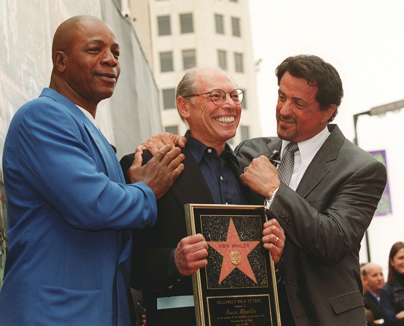 "FILE – In this April 28, 2000, file photo, actor and screenwriter Sylvester Stallone, right, and his ""Rocky"" co-star, former professional football player Carl Weathers, left, pose with producer Irwin Winkler at the Walk of Fame ceremony for Winkler in the Hollywood section of Los Angeles. Four decades after the Nov. 21, 1976, premiere of ""Rocky,"" the movie's reach is international, and the title character's underdog tale of determination, grit and sleepy-eyed charm still resonates with fans. (AP Photo/Chris Pizzello, File)"