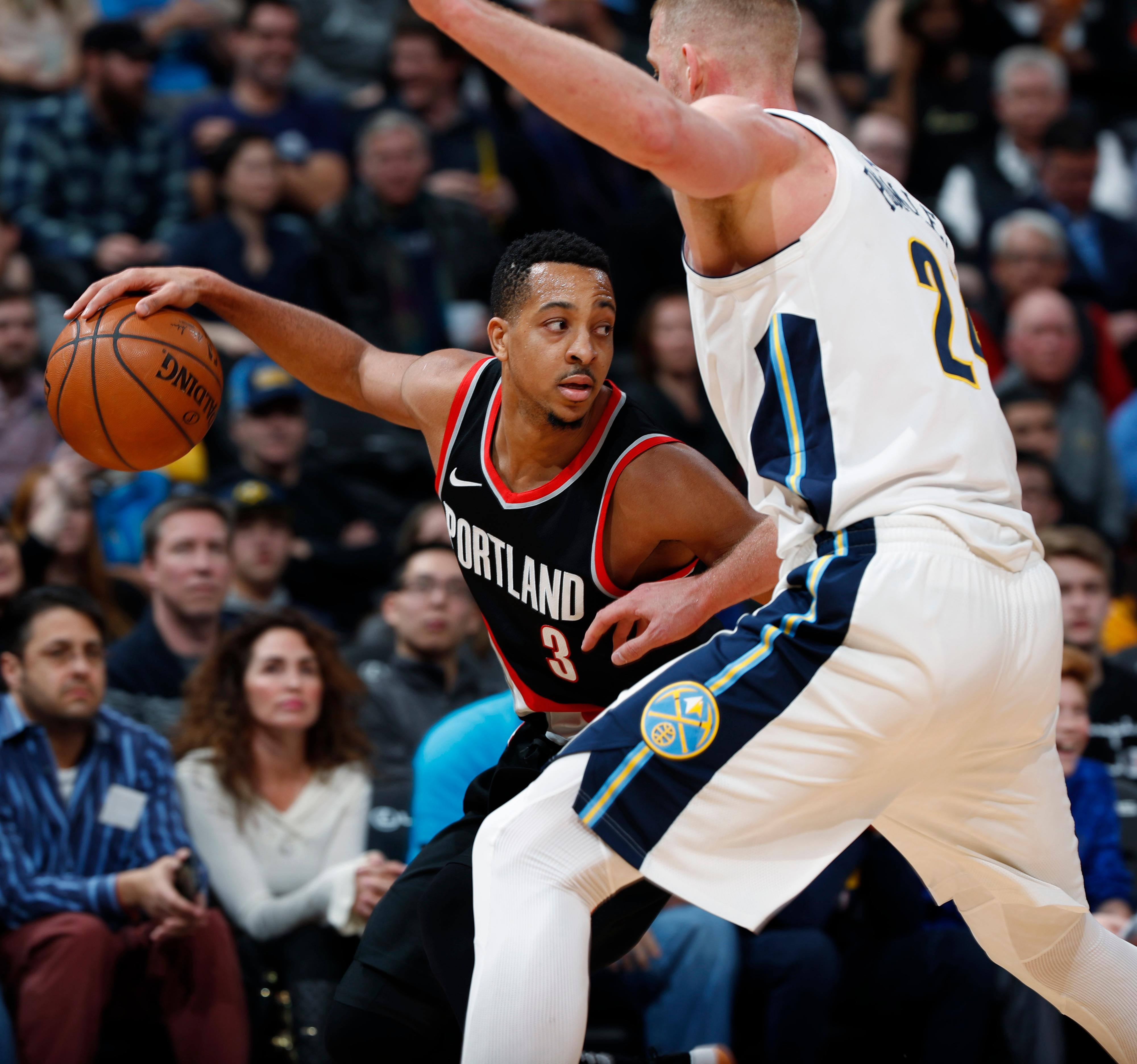 Portland Trail Blazers guard CJ McCollum, left, tries to drive past Denver Nuggets center Mason Plumlee in the second half of an NBA basketball game Monday, Jan. 22, 2018, in Denver. The Nuggets 104-101. (AP Photo/David Zalubowski)