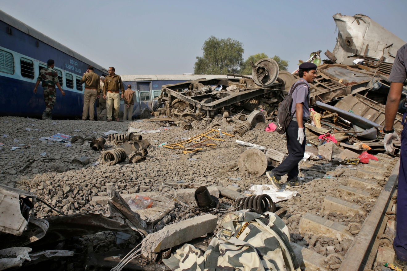 Rescuers and policemen walk near debris after 14 coaches of an overnight passenger train rolled off the track near Pukhrayan village Kanpur Dehat district, Uttar Pradesh state, India, Sunday, Nov. 20, 2016. Dozens were killed and dozens more were injured in the accident. (AP Photo/Rajesh Kumar Singh)