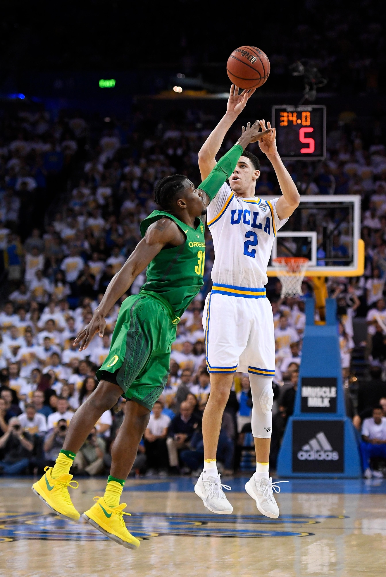 UCLA guard Lonzo Ball, right, shoots as Oregon guard Dylan Ennis defends during the second half of an NCAA college basketball game, Thursday, Feb. 9, 2017, in Los Angeles. UCLA won 82-79. (AP Photo/Mark J. Terrill)
