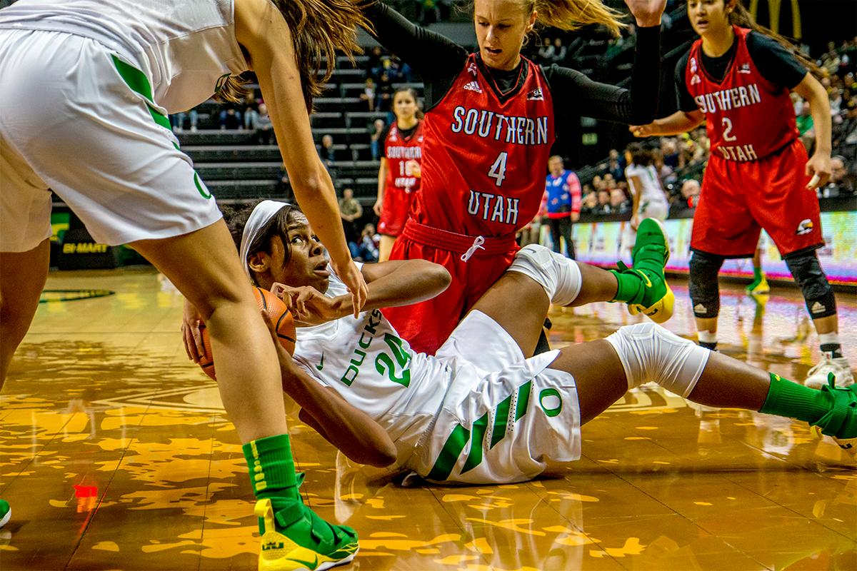 The Duck's Ruthy Hebard (#24) passes the ball off to a teammate as she takes a tumble. The University of Oregon Ducks women basketball team defeated the Southern Utah Thunderbirds 98-38 in Matthew Knight Arena Saturday afternoon. The Ducks had four players in double-digits: Ruthy Hebard with 13; Mallory McGwire with 10; Lexi Bando with 17 which included four three-pointers; and Sabrina Ionescu with 16 points. The Ducks overwhelmed the Thunderbirds, shooting 50% in field goals to South Utah's 26.8%, 53.8% in three-pointers to 12.5%, and 85.7% in free throws to 50%. The Ducks, with an overall record of 8-1, and coming into this game ranked 9th, will play their next home game against Ole Miss on December 17. Photo by August Frank, Oregon News Lab