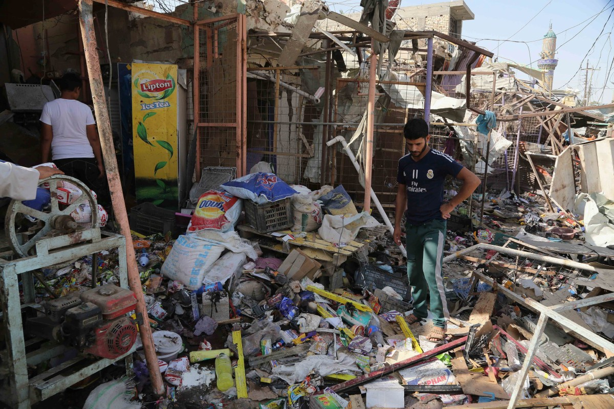 Civilians gather at the scene of a suicide car bombing at a busy market in Khan Bani Saad in the Diyala province, about 20 miles (30 kilometers) northeast of Baghdad, Iraq, Saturday, July 18, 2015. A suicide car bombing in Iraq's eastern Diyala province killed at least 80 people gathered at a marketplace to mark the end of the holy month of Ramadan on Friday. (AP Photo/Karim Kadim)