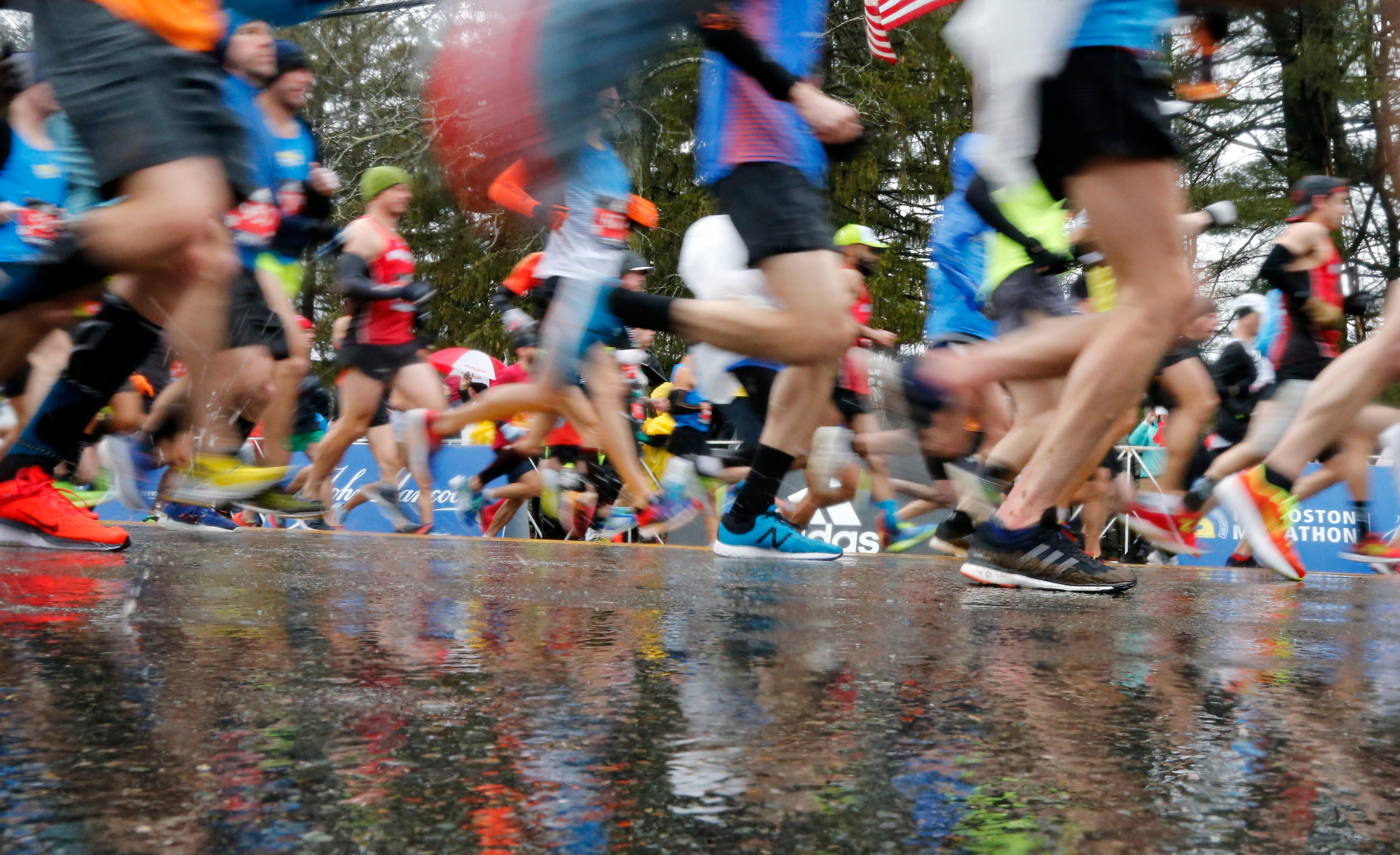 Runners in the first wave break from the start on rain soaked streets during the 122nd running of the Boston Marathon in Hopkinton, Mass., Monday, April 16, 2018. (AP Photo/Mary Schwalm)