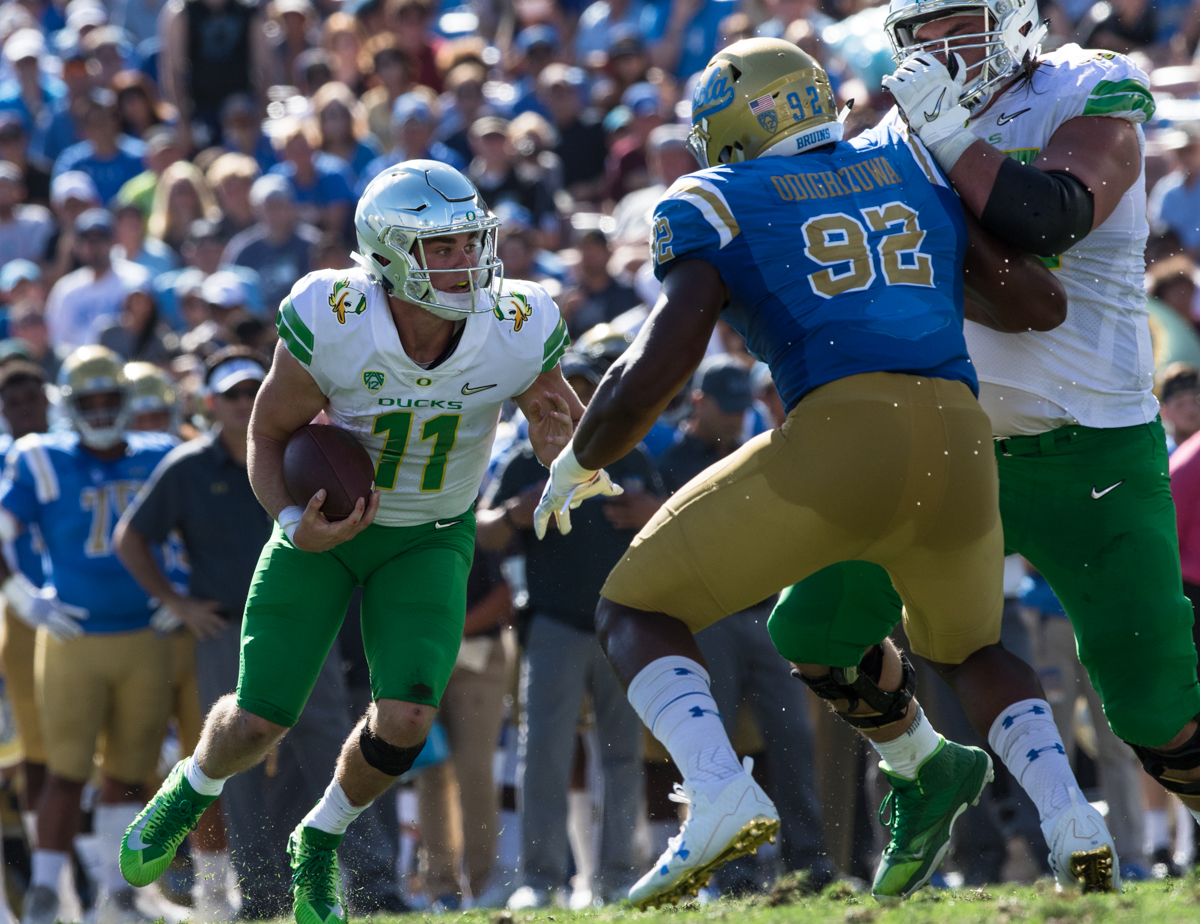 Oregon quarterback Braxton Burmeister (#11) runs the ball on a quarterback scramble. The Oregon Ducks rallied during the second quarter to go into halftime tied 14-14 with the UCLA Bruins at Rose Bowl Stadium in Pasadena, California. Photo by Austin Hicks, Oregon News Lab