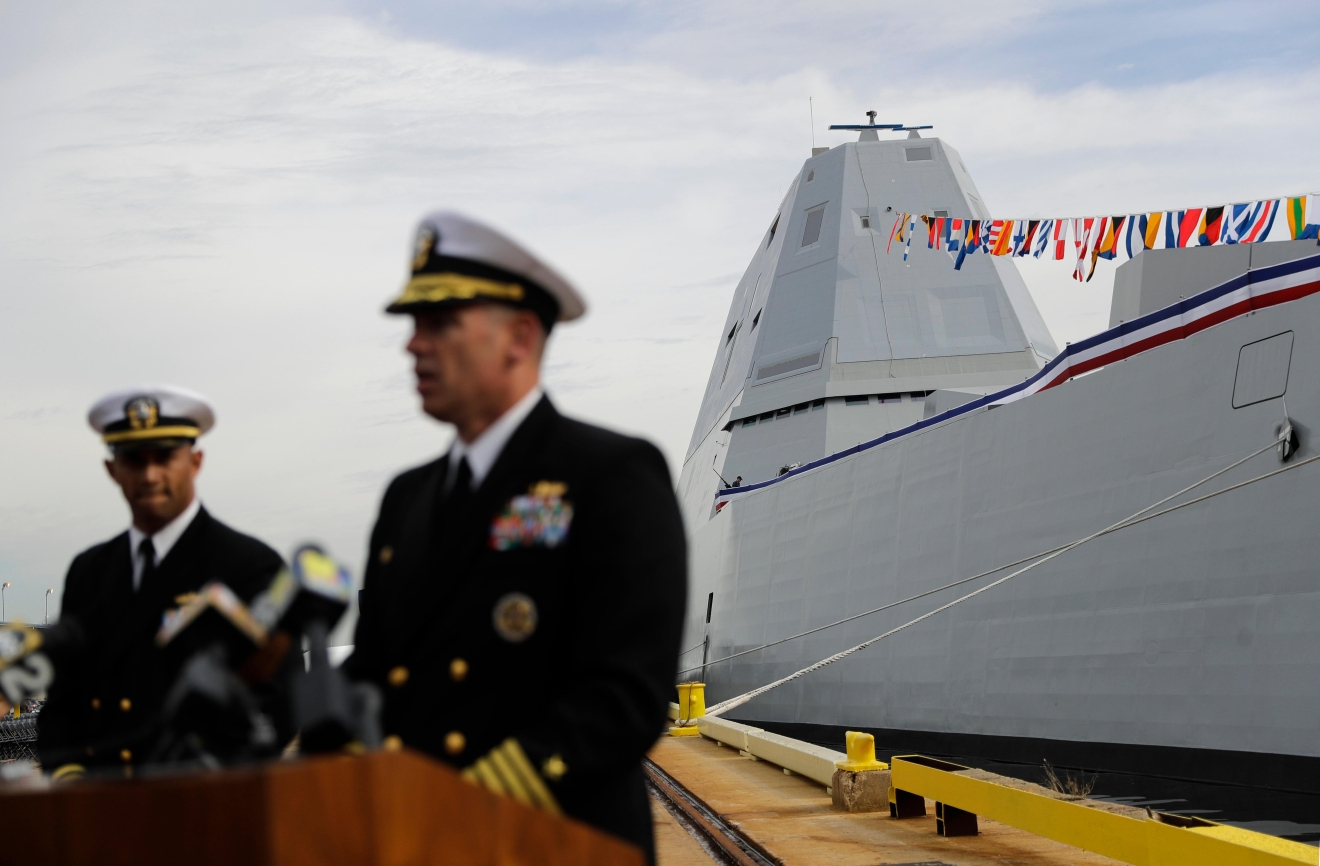 "In this Oct. 13, 2016 photo, the future USS Zumwalt is seen docked behind Capt. James Kirk, second from left, commanding officer of the ship, as Kirk speaks at a news conference in Baltimore. It is named after the late Adm. Elmo ""Bud"" Zumwalt, the youngest chief of naval operations who earned a reputation as a reformer. (AP Photo/Patrick Semansky)"