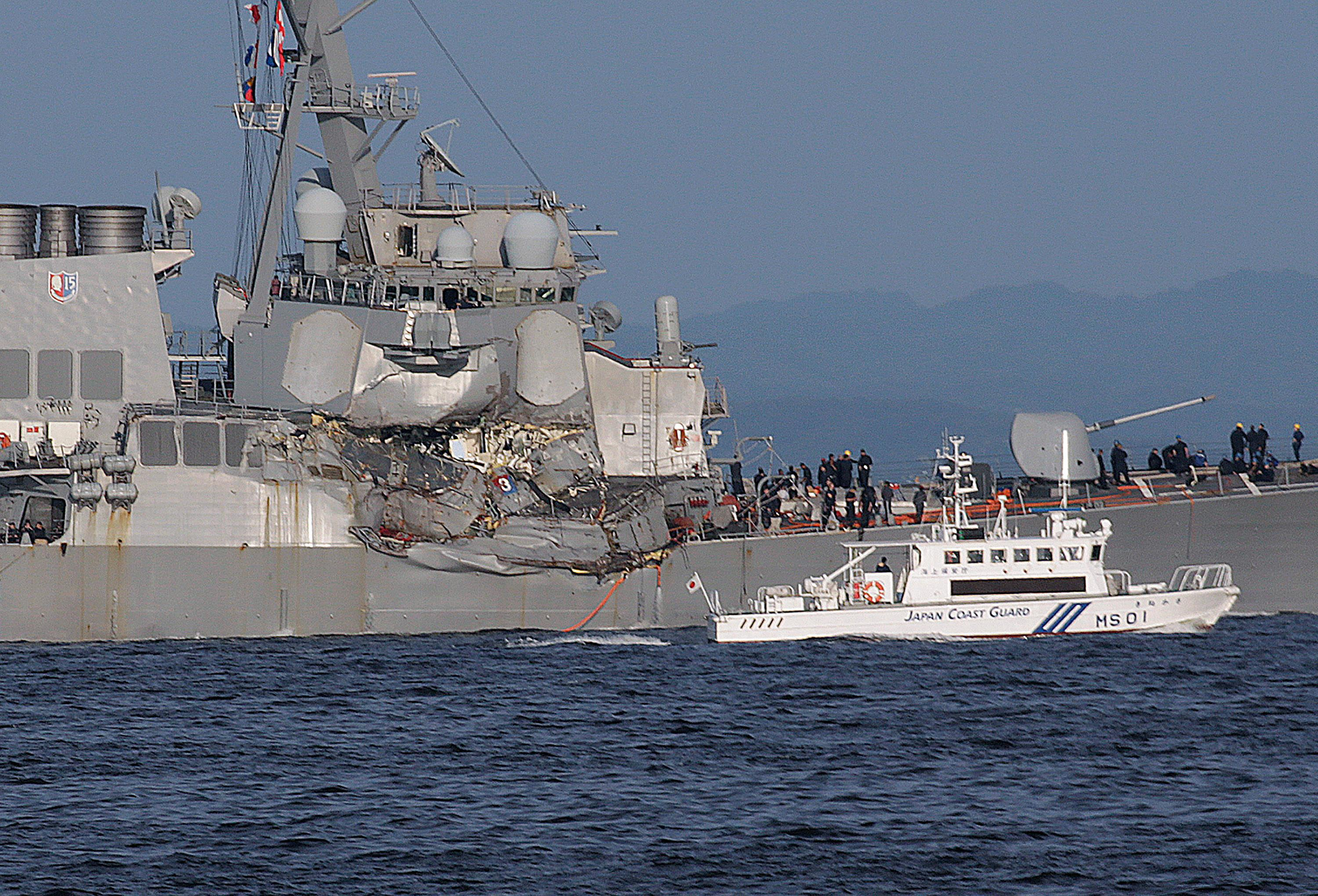 A Japan Coast Guard ship, foreground, navigates the damaged USS Fitzgerald near the U.S. Naval base in Yokosuka, southwest of Tokyo, after the U.S. destroyer collided with the Philippine-registered container ship ACX Crystal in the waters off the Izu Peninsula Saturday, June 17, 2017. The USS Fitzgerald was back at its home port in Japan after colliding before dawn Saturday with a container ship four times its size, while the coast guard and Japanese and U.S. military searched for seven sailors missing after t