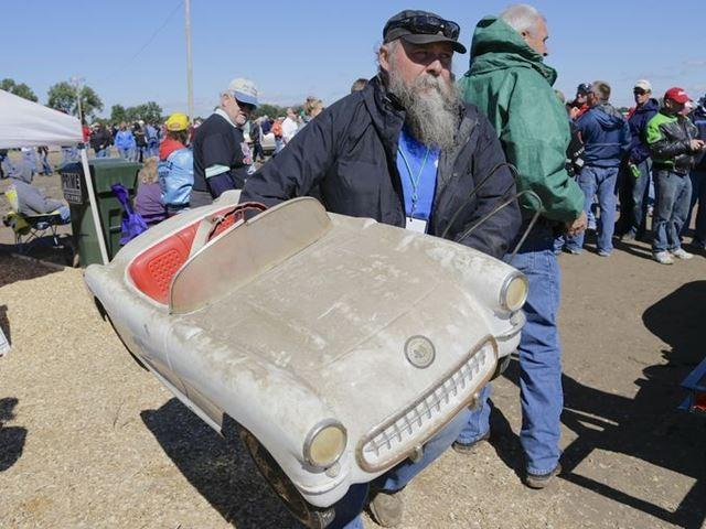 An auction employee moves a 1953 Corvette toy pedal car after it sold for $16,000 in the auction of vehicles, parts and memorabilia from the former Lambrecht Chevrolet dealership in Pierce Neb.