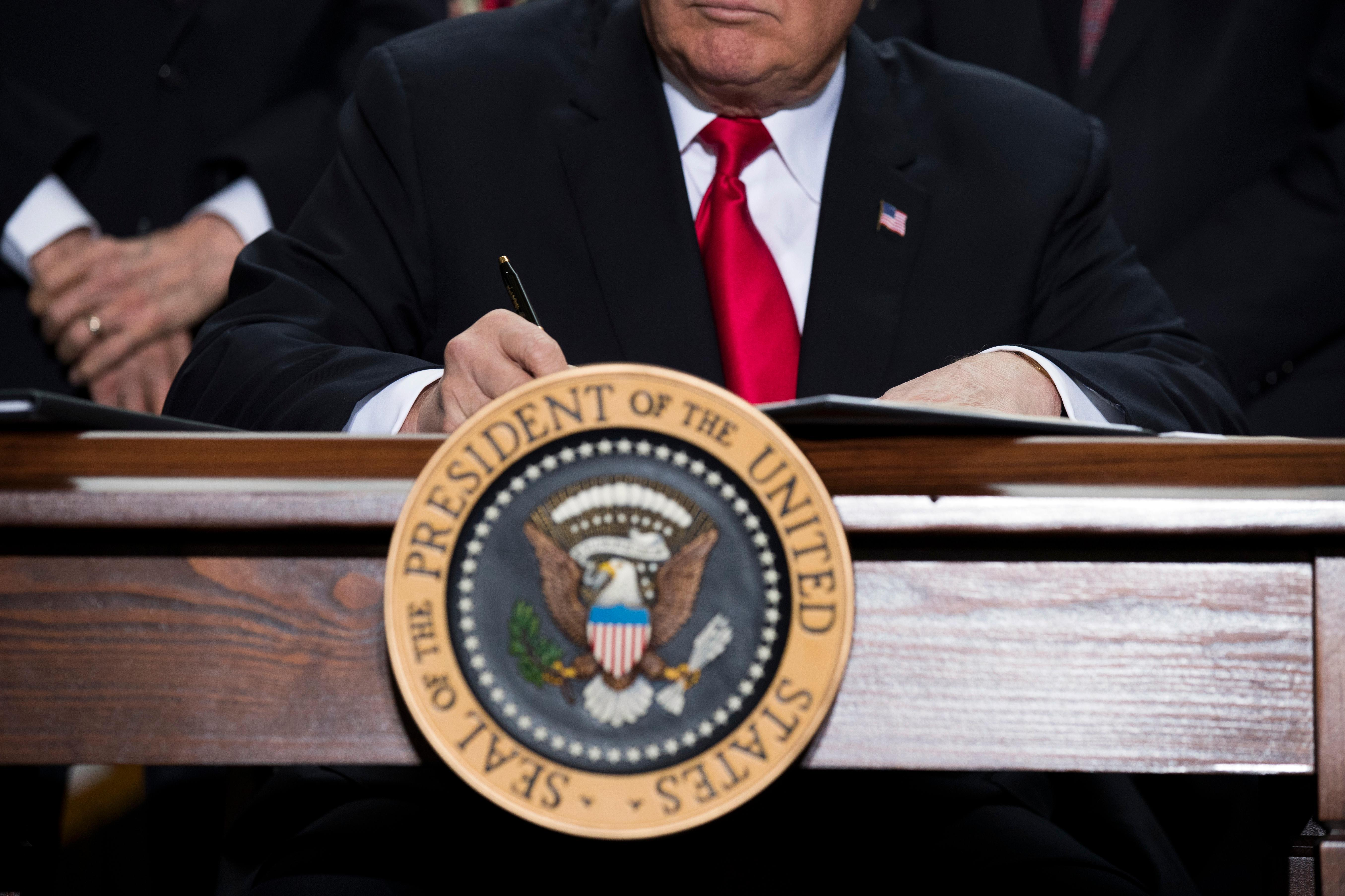 President Donald Trump signs a proclamation to shrink the size of Bears Ears and Grand Staircase Escalante national monuments, Monday, Dec. 4, 2017, in Salt Lake City. (AP Photo/Evan Vucci)