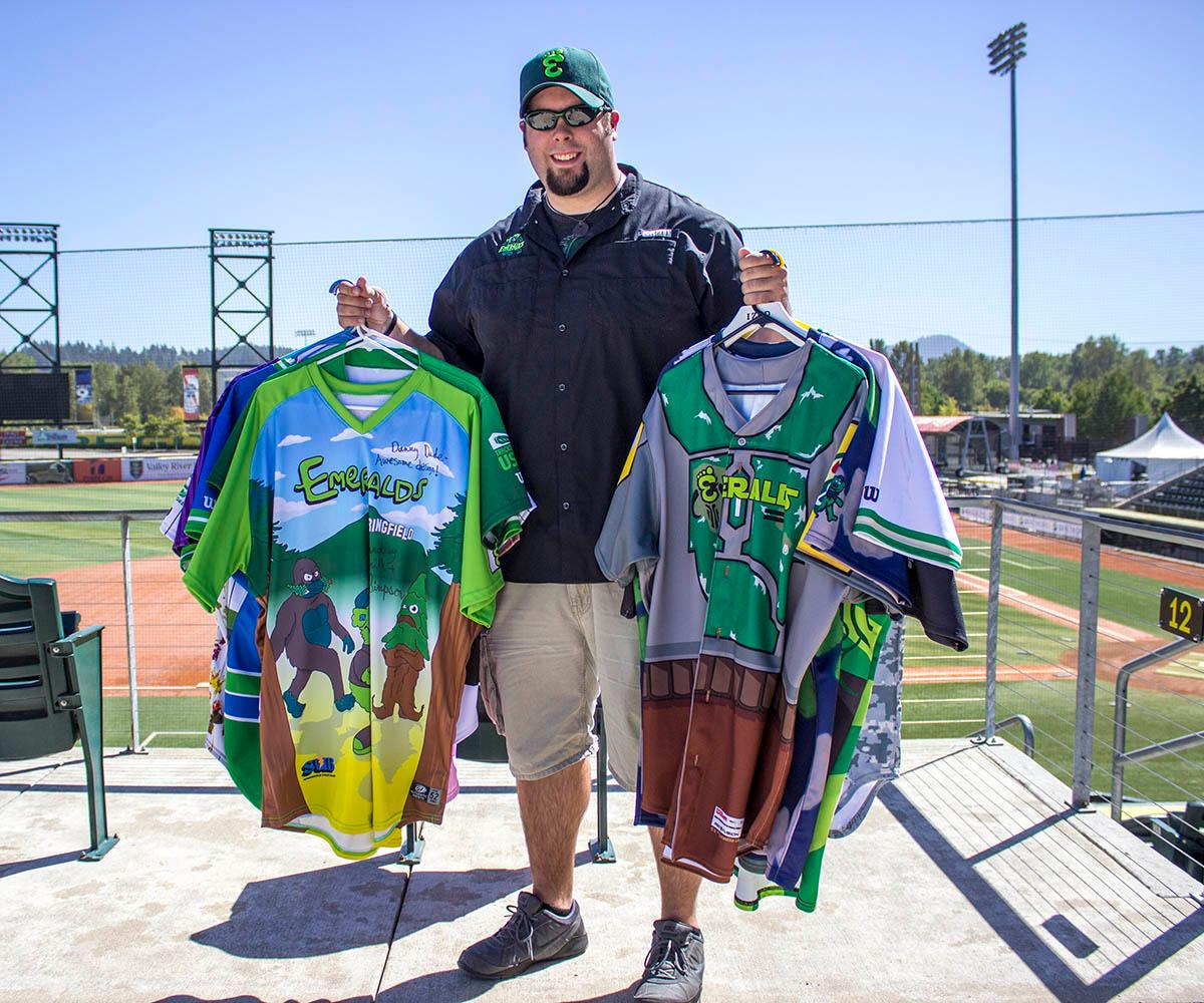 Eugene Emeralds graphic designer holds up dozens of jerseys he designed since he started working for the team in 2012. The Eugene Emeralds will hold a Throwback Thursday and Teacher Appreciation Night August 18. Teachers can get free box seats. (Photo by Amanda Butt)