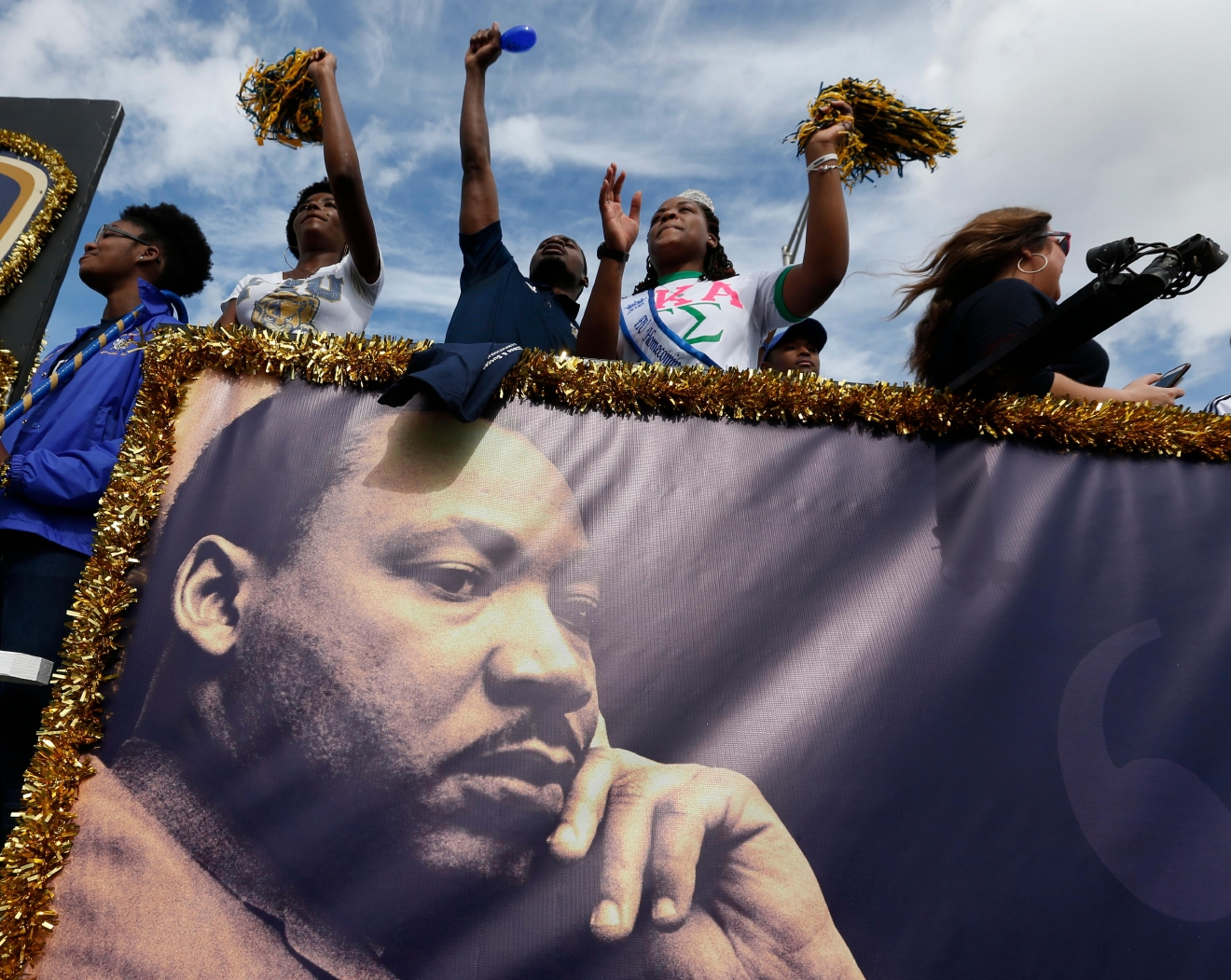 People aboard a float from Florida International University wave to crowds during a parade honoring the Rev. Martin Luther King Jr., Monday, Jan. 16, 2017, in the Liberty City neighborhood of Miami. (AP Photo/Wilfredo Lee)