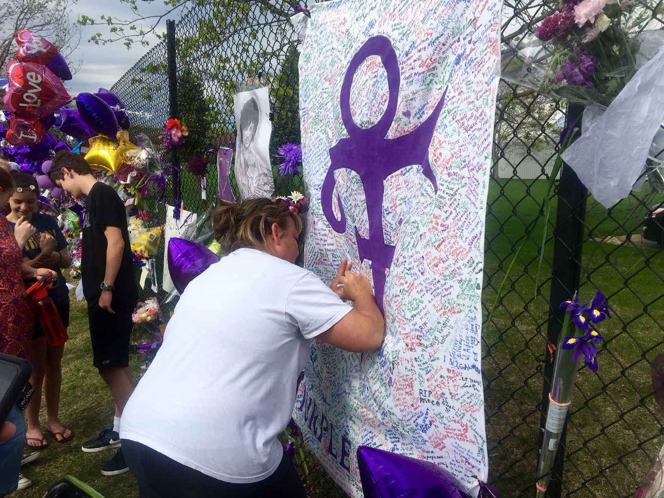 A woman writes on memorial sheet adorned with the symbol Prince once used to identify himself outside Paisley Park in Chanhassen, Minn., Saturday, April 23, 2016. The music superstar was pronounced dead at his Paisley Park estate near Minneapolis on Thursday. He was 57. (AP Photo/Jeff Baenen)