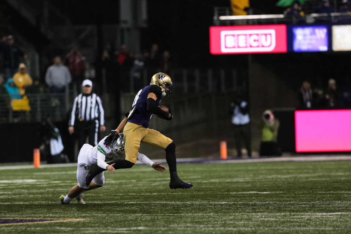 Washington punt-returner Dante Pettis (#8) sheds the final Oregon tackler and returns a punt for a touchdown, breaking the NCAA record for punt-return touchdowns. The Oregon Ducks are trailing the Washington Huskies 3 - 17 at halftime.  The Huskies rallied with a 17-point second quarter after a slow first quarter on a cold and rainy night in Seattle, Washington.  Photo by Austin Hicks, Oregon News Lab