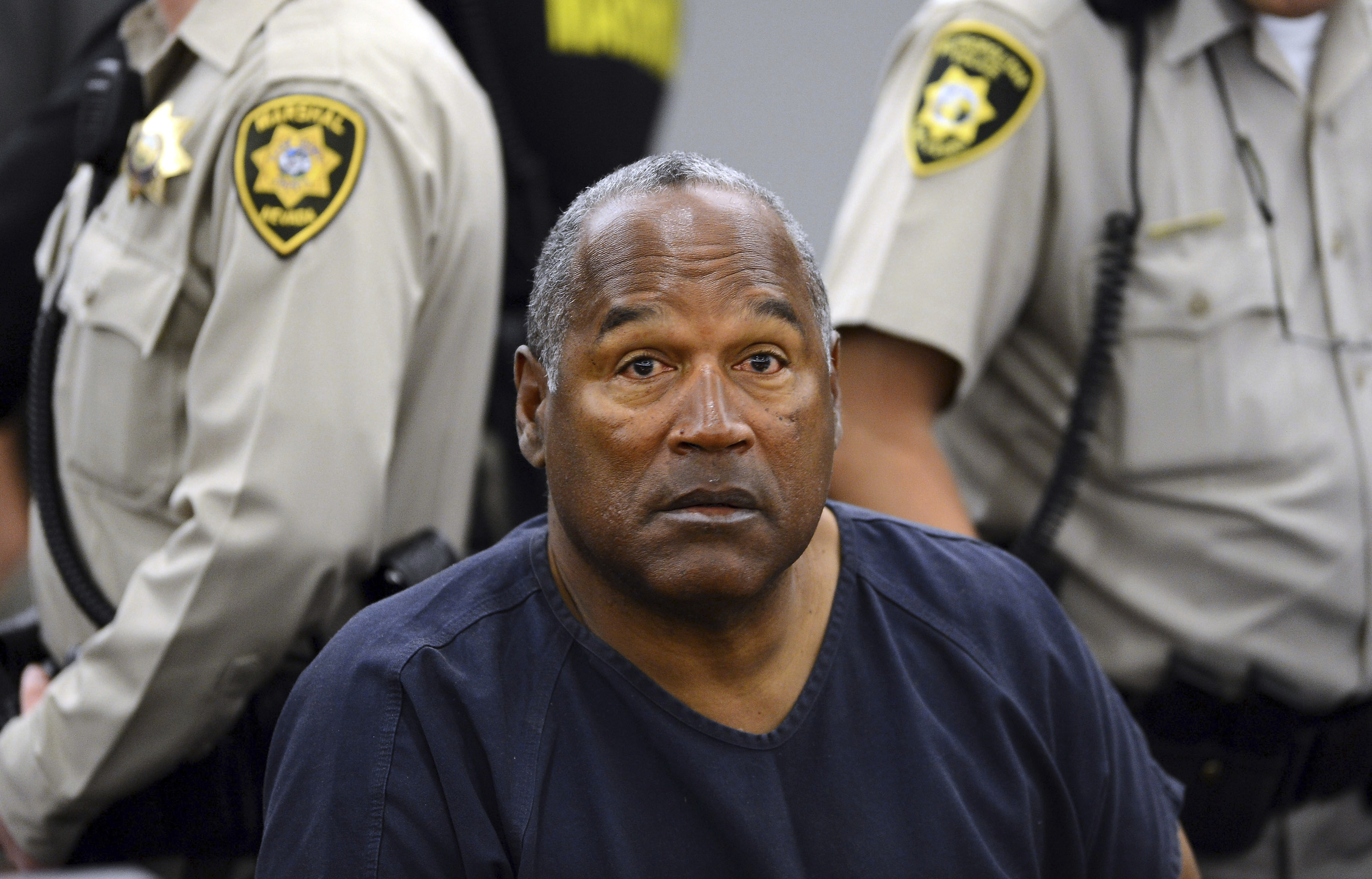 FILE - In this May 14, 2013, pool file photo, O.J. Simpson sits during a break on the second day of an evidentiary hearing in Clark County District Court in Las Vegas. Simpson, the former football star, TV pitchman and now Nevada prison inmate, will have a lot going for him when he appears before state parole board members Thursday, July 20, 2017 seeking his release after more than eight years for an ill-fated bid to retrieve sports memorabilia. A Nevada prison official said early Sunday, Oct. 1, 2017, O.J. Simpson, the former football legend and Hollywood star, has been released from a Nevada prison in Lovelock after serving nine years for armed robbery. (AP Photo/Ethan Miller, Pool, File)