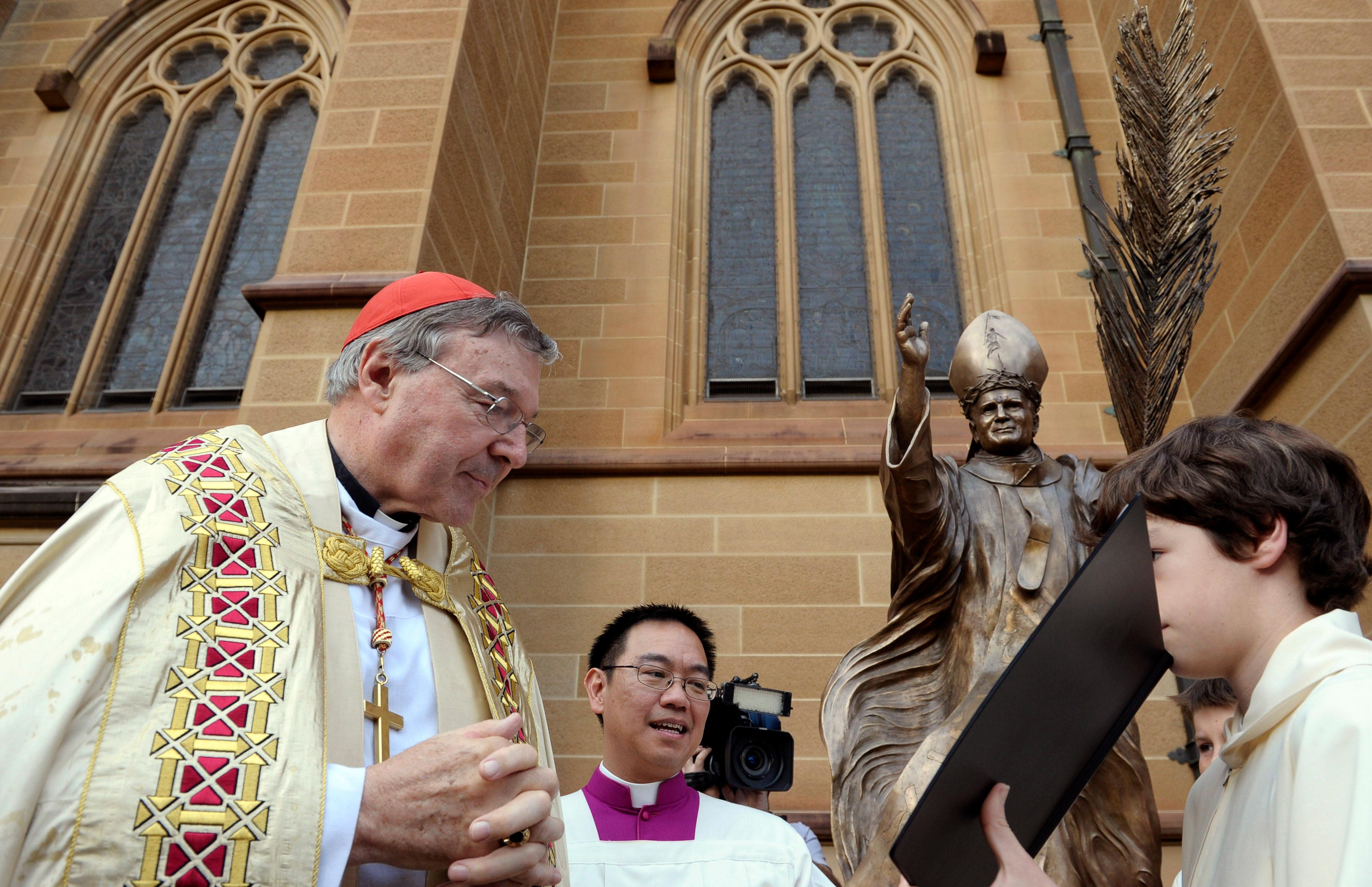 FILE - In this May 1, 2011 file photo, Cardinal George Pell, left, reads a bible during the blessing of a statue of John Paul ll at St Mary's Cathedral in Sydney, Australia. Australian police say they are charging Pell with historical sexual assault offenses. (AP Photo/Rob Griffith, File)