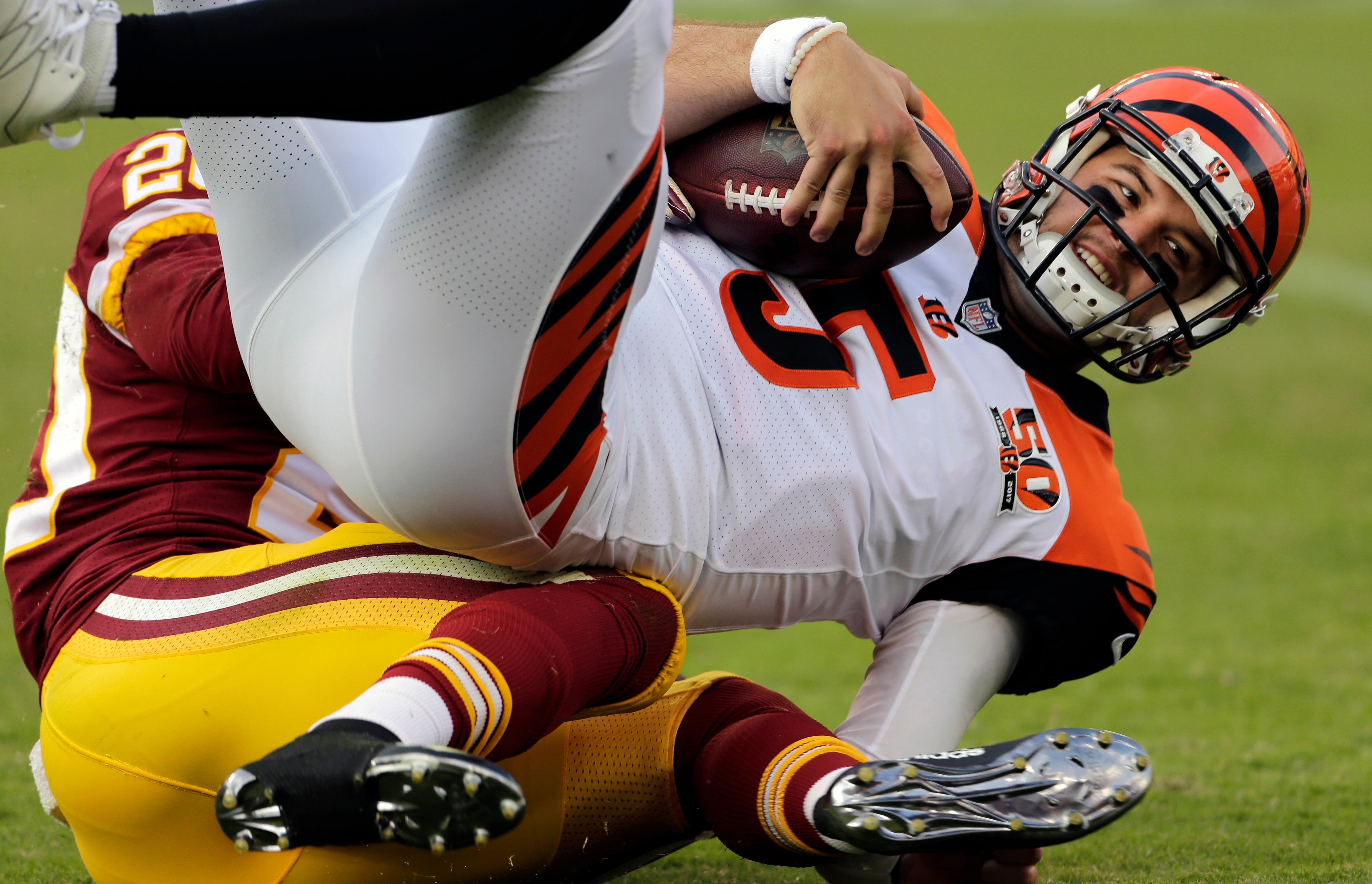 Cincinnati Bengals quarterback AJ McCarron, top, is sacked by Washington Redskins defensive back Joshua Holsey in the second half of a preseason NFL football game, Sunday, Aug. 27, 2017, in Landover, Md. (AP Photo/Mark Tenally)