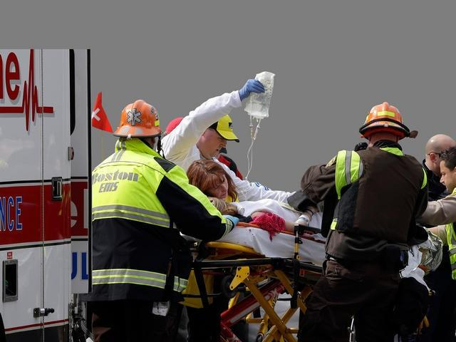 Medical workers put injured into an ambulance outside the medical tent at the finish area following explosions near the finish line of the 2013 Boston Marathon.
