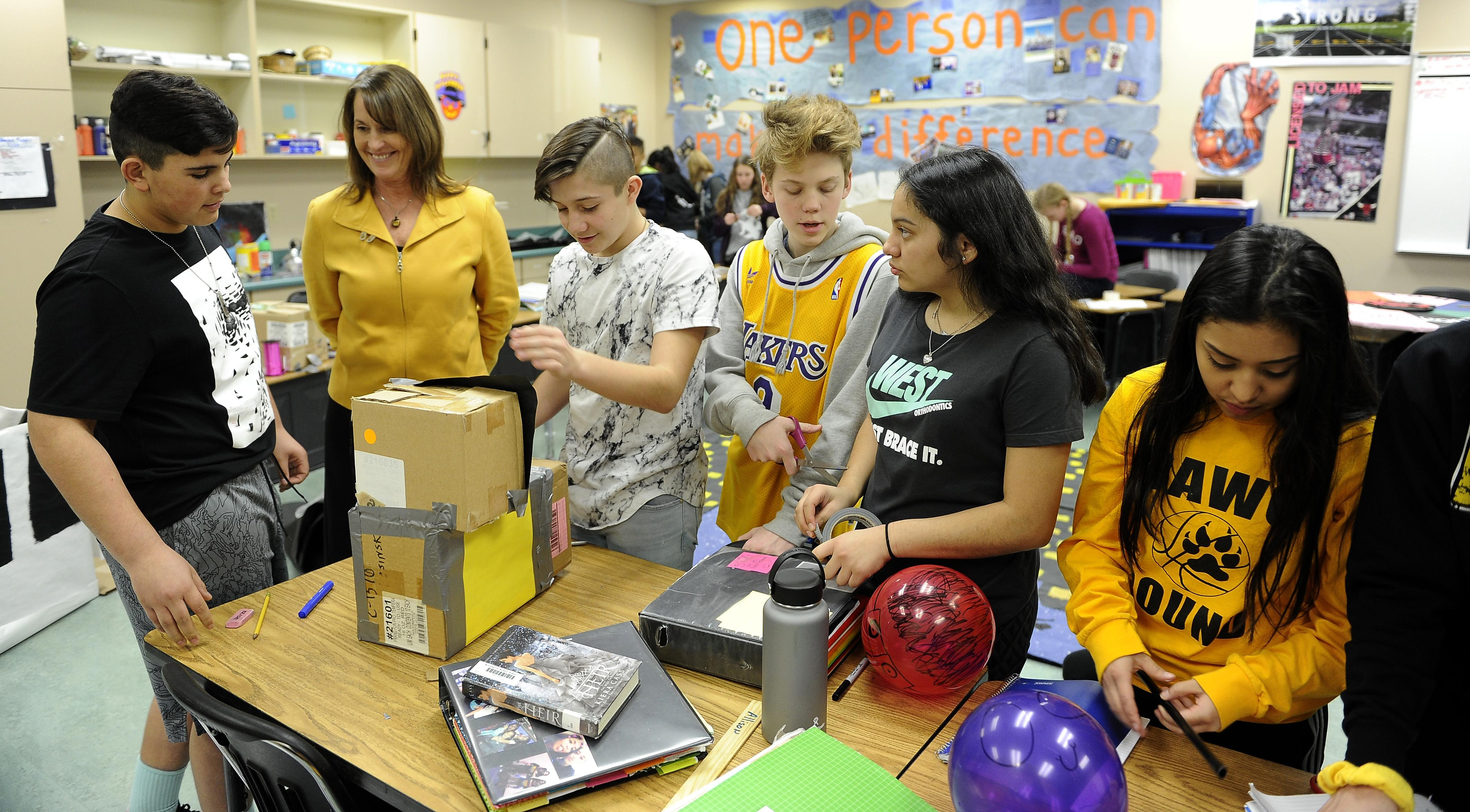 McLoughlin Middle School Principal Linda White works with students on art projects for an upcoming school dance. [Mail Tribune / Andy Atkinson]