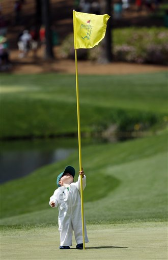 Scott Stallings's son Finn looks at the flag on the fourth green during the par three competition at the Masters golf tournament Wednesday, April 9, 2014, in Augusta, Ga.