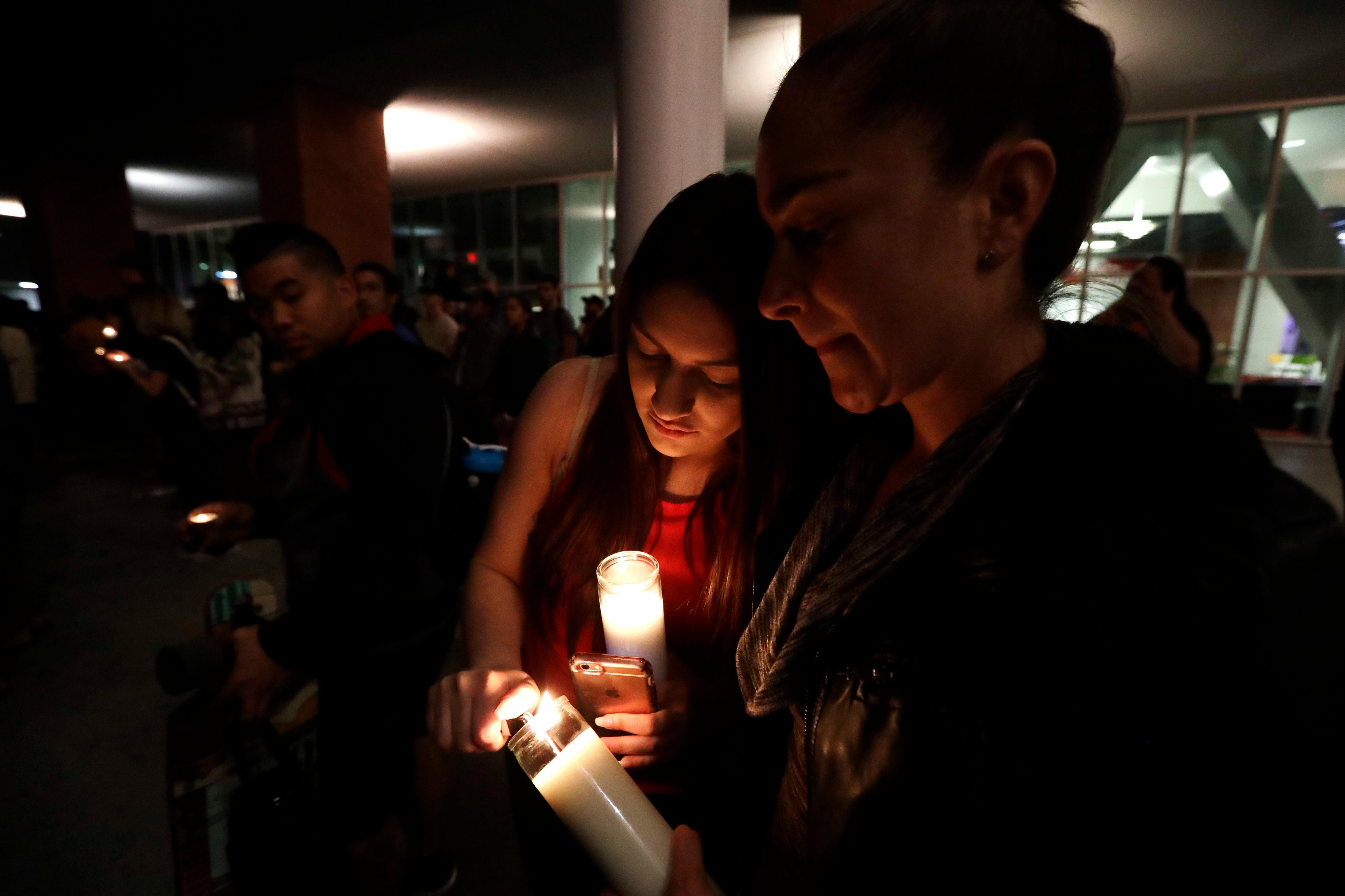 Virginia, right, and Natalie Ramos light candles as students from University of Nevada Las Vegas hold a vigil Monday, Oct. 2, 2017, in Las Vegas. A gunman on the 32nd floor of the Mandalay Bay casino hotel rained automatic weapons fire down on the crowd of over 22,000 at an outdoor country music festival Sunday. (AP Photo/Gregory Bull)