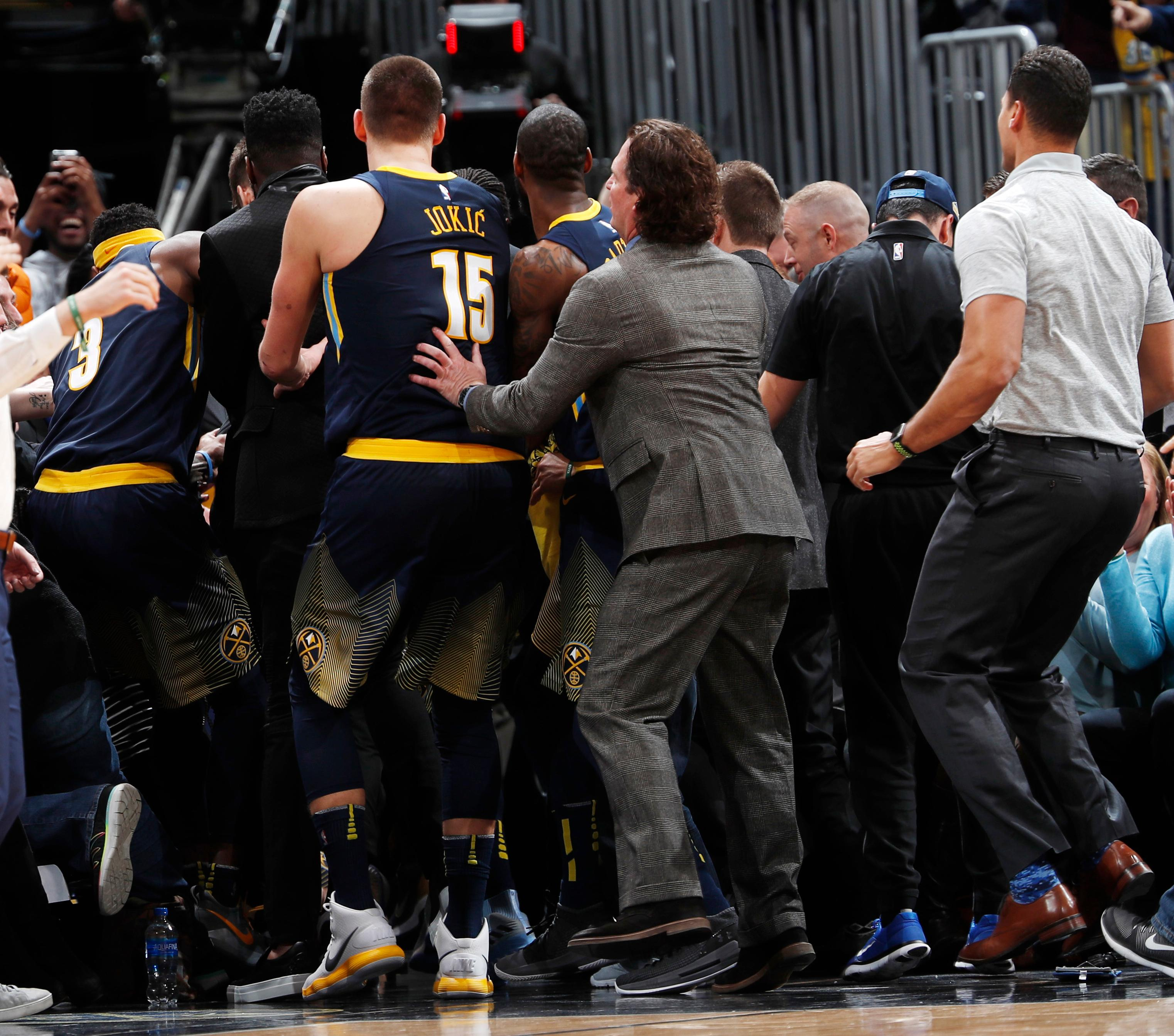 Members of the Denver Nuggets surround guard Gary Harris after he hit a 3-point basket at the final buzzer in the team's NBA basketball game against the Oklahoma City Thunder on Thursday, Feb. 1, 2018, in Denver. The Nuggets won 127-124. (AP Photo/David Zalubowski)