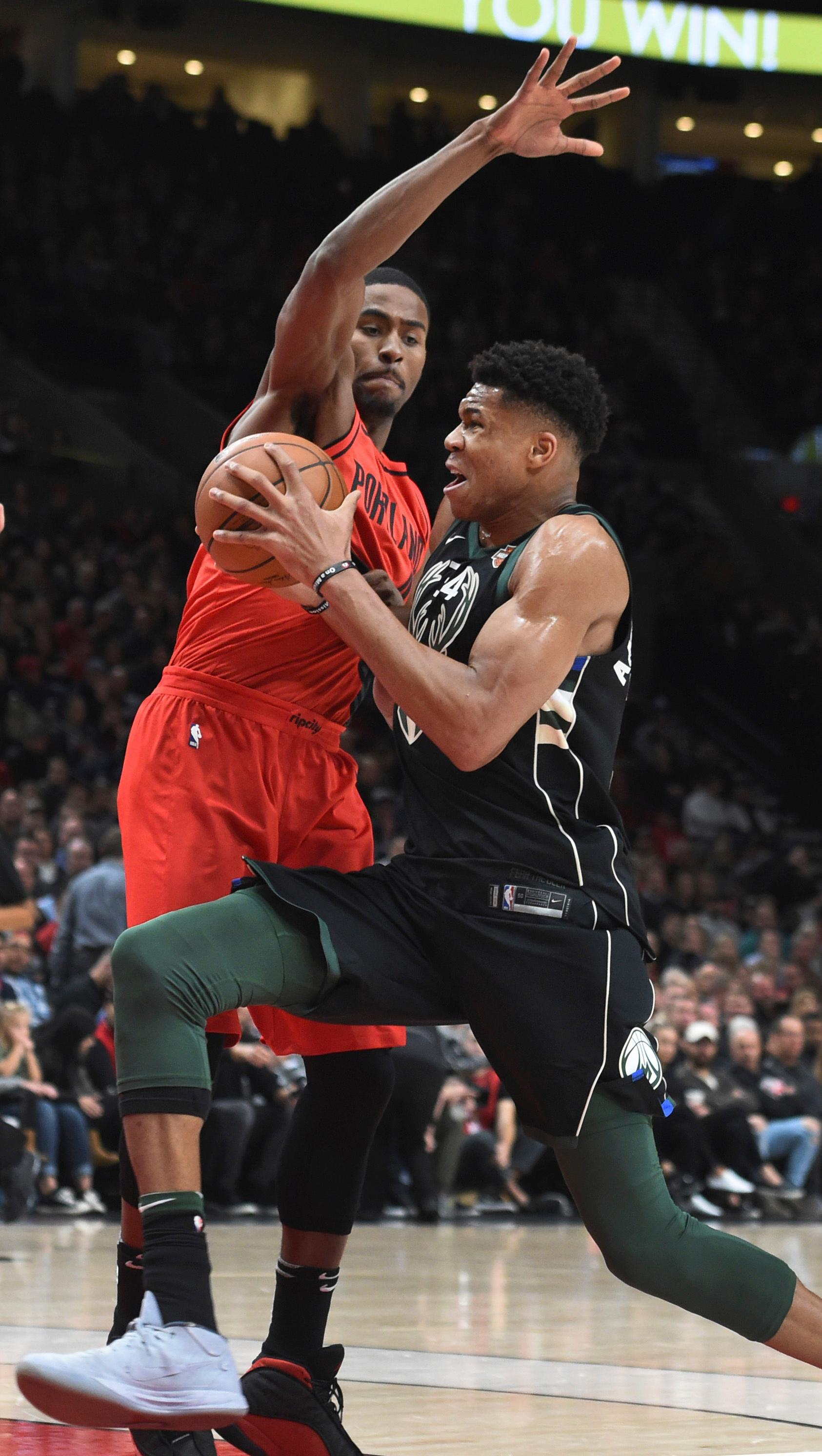 Milwaukee Bucks forward Giannis Antetokounmpo drives to the basket on Portland Trail Blazers forward Maurice Harkless during the first quarter of an NBA basketball game in Portland, Ore., Thursday, Nov. 30, 2017. (AP Photo/Steve Dykes)
