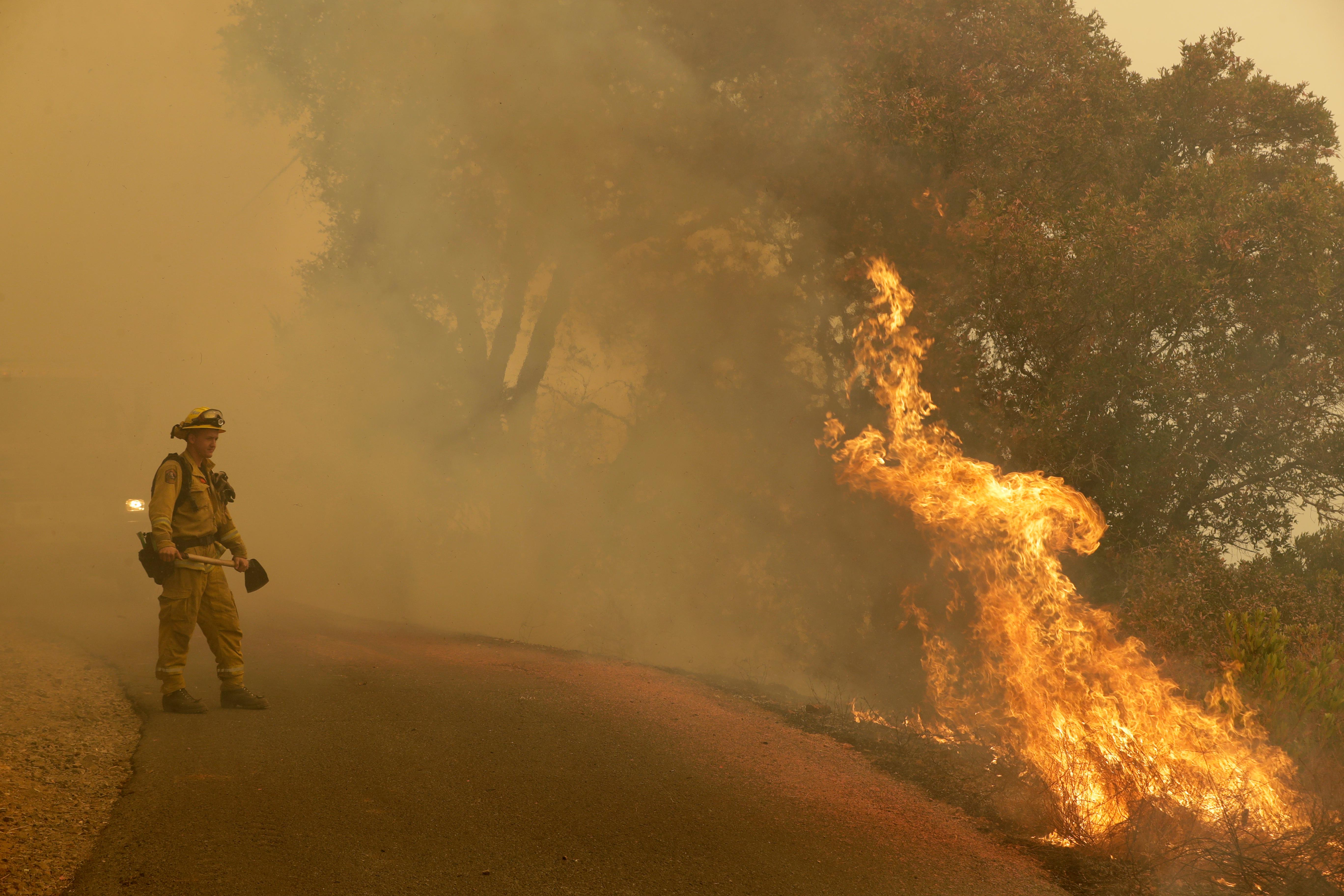 A firefighter monitors flames from a blackburn operation Friday, Oct. 13, 2017, in Glen Ellen, Calif. (AP Photo/Marcio Jose Sanchez)