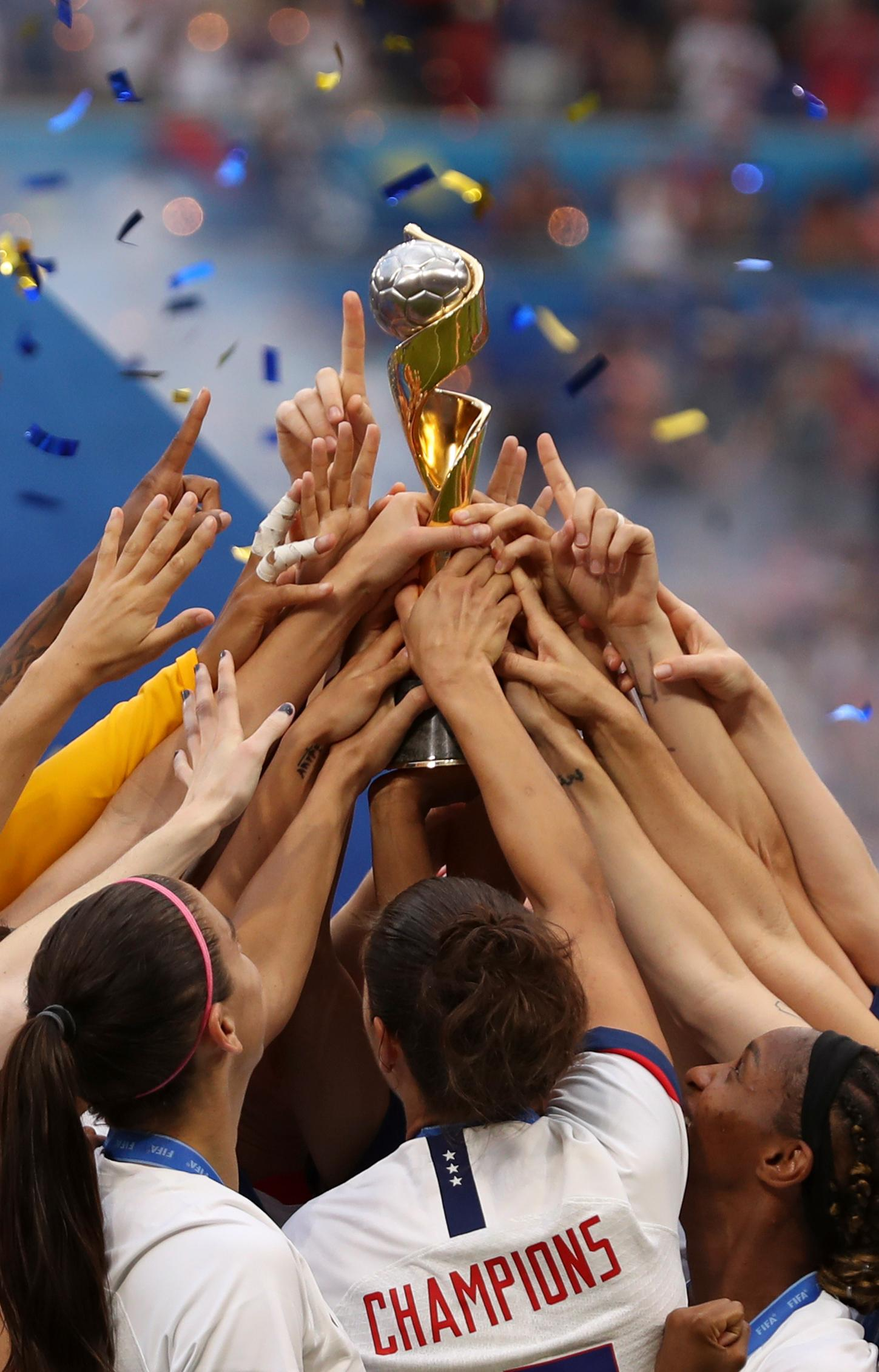 The United States players hold the trophy celebrating at the end of the Women's World Cup final soccer match between US and The Netherlands at the Stade de Lyon in Decines, outside Lyon, France, Sunday, July 7, 2019. The US defeated the Netherlands 2-0. (AP Photo/Francisco Seco)