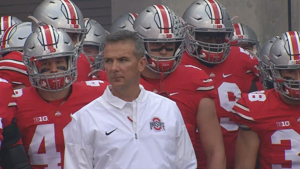 Alexis - Urban Meyer with football team.jpg