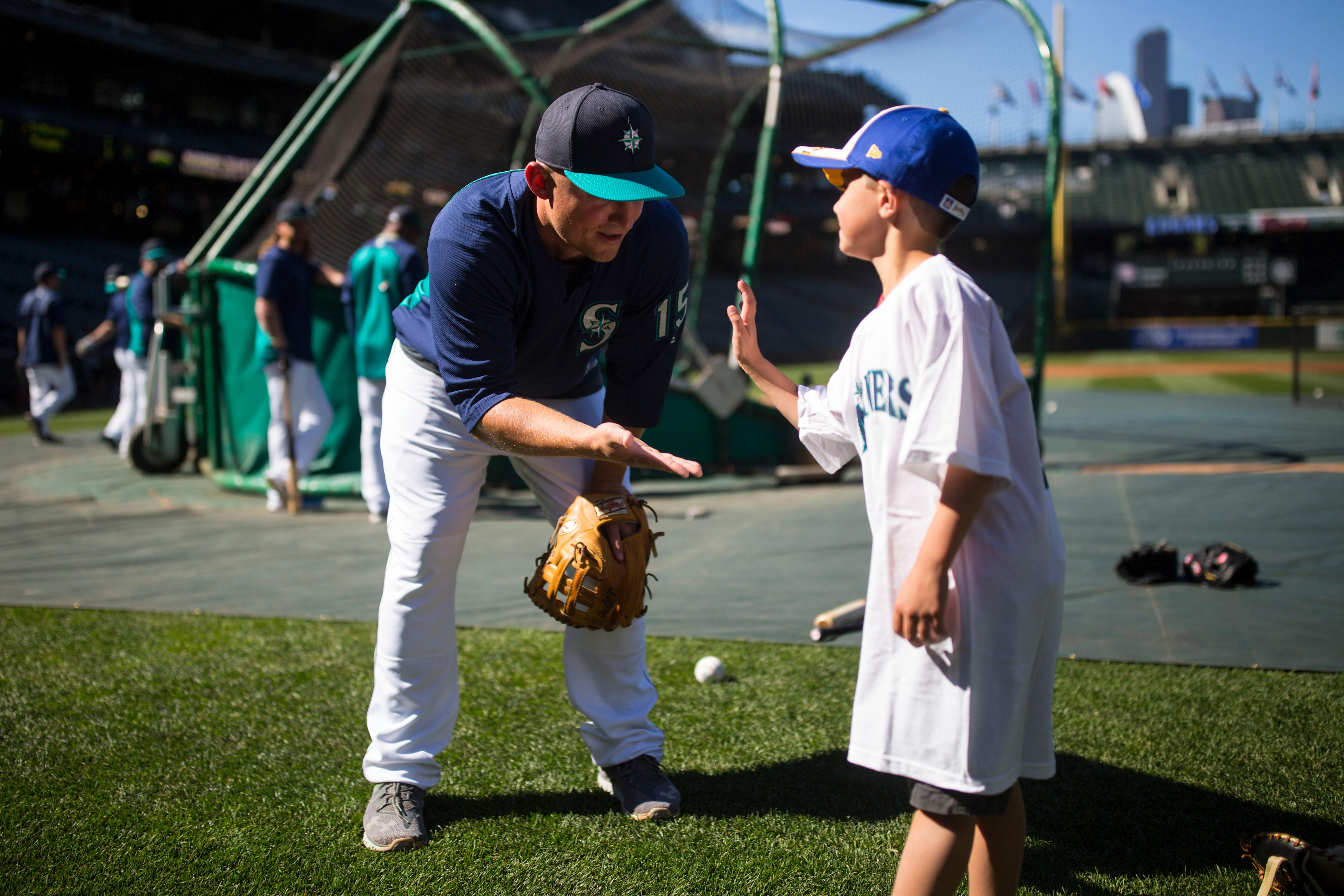 "Seven-year-old kidney cancer survivor Mason Nettleton high fives Seattle Mariner Kyle Seager as Nettleton served Seattle as a ""Superhero for a Day"" on Tuesday, June 27, 2017. (Sy Bean / Seattle Refined)"
