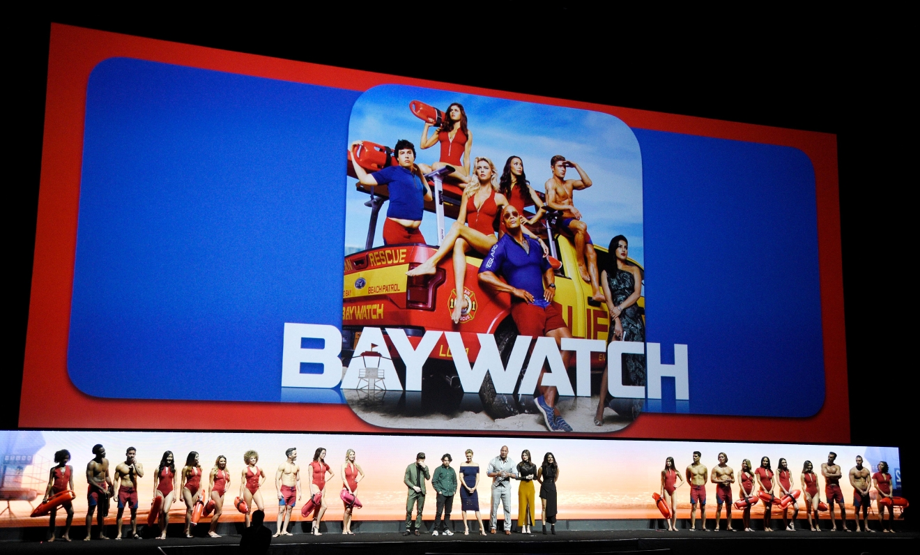 "The cast of ""Baywatch,"" bottom center, Zac Efron, from center left, Jon Bass, Kelly Rohrbach, Dwayne Johnson, Alexandra Daddario and Priyanka Chopra, are flanked by models dressed as lifeguards during the Paramount Pictures presentation at CinemaCon 2017 at Caesars Palace on Tuesday, March 28, 2017, in Las Vegas. (Photo by Chris Pizzello/Invision/AP)"
