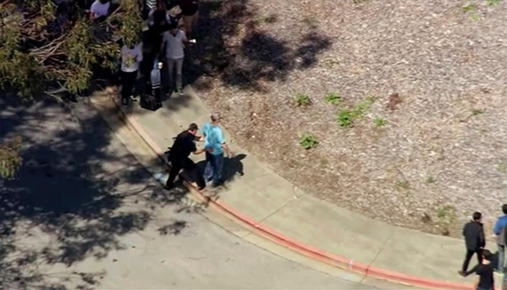 This image taken from video from KGO-TV shows a person is searched as police respond to reports of a shooting at YouTube headquarters in the city of San Bruno, Calif., on Tuesday, April 3, 2018. City Manager Connie Jackson says there have been multiple 911 calls reporting a shooting and that police and fire officials have responded.  (KGO-TV via AP)