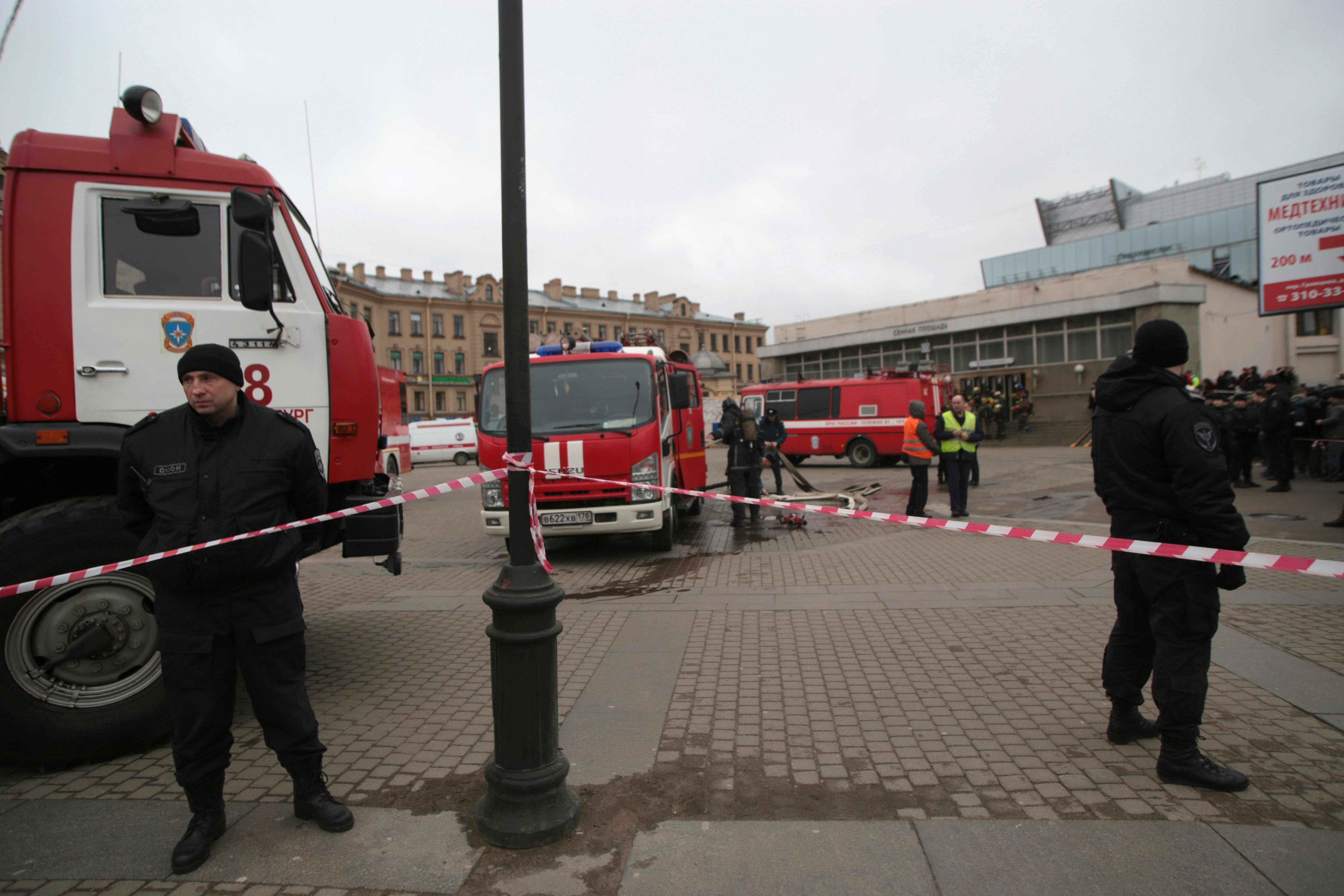 Russian police and emergency service officers stand near fire trucks near the entrance of Sennaya Square subway station in St. Petersburg, Russia, Monday, April 3, 2017. The subway in the Russian city of St. Petersburg is reporting that there are fatalities and several people have been injured in an explosion on a subway train. (AP Photo/Evgenii Kurskov)