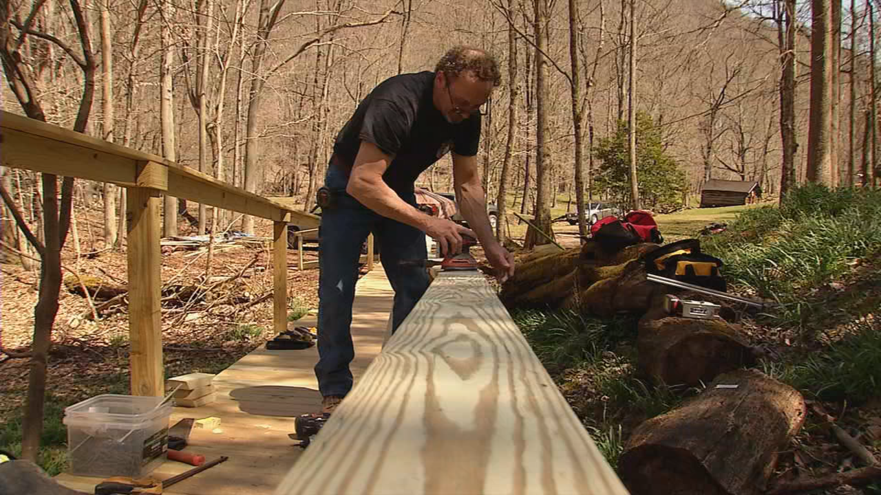 Contractor Mark Rumney sands a handrail along the new boardwalk. (WCHS/WVAH)