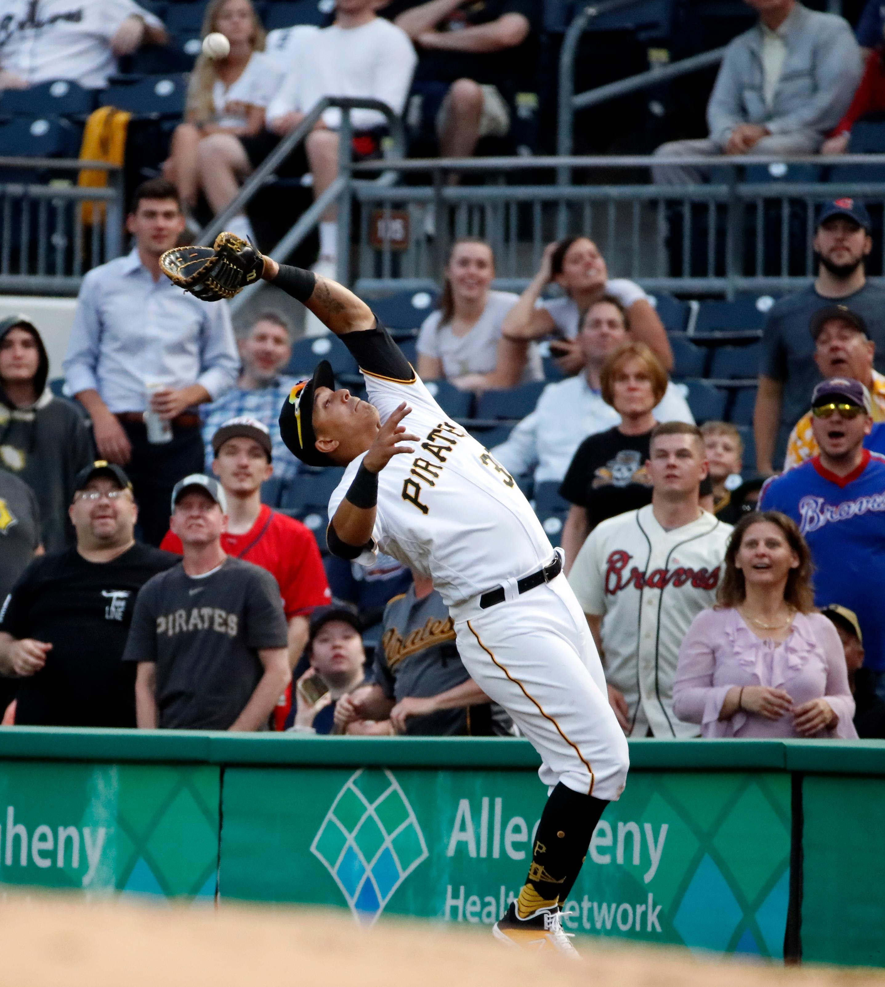 Pittsburgh Pirates first baseman Jose Osuna falls backward as he makes the catch on a pop foul by Atlanta Braves' Austin Riley during the third inning of a baseball game in Pittsburgh, Tuesday, June 4, 2019. (AP Photo/Gene J. Puskar)