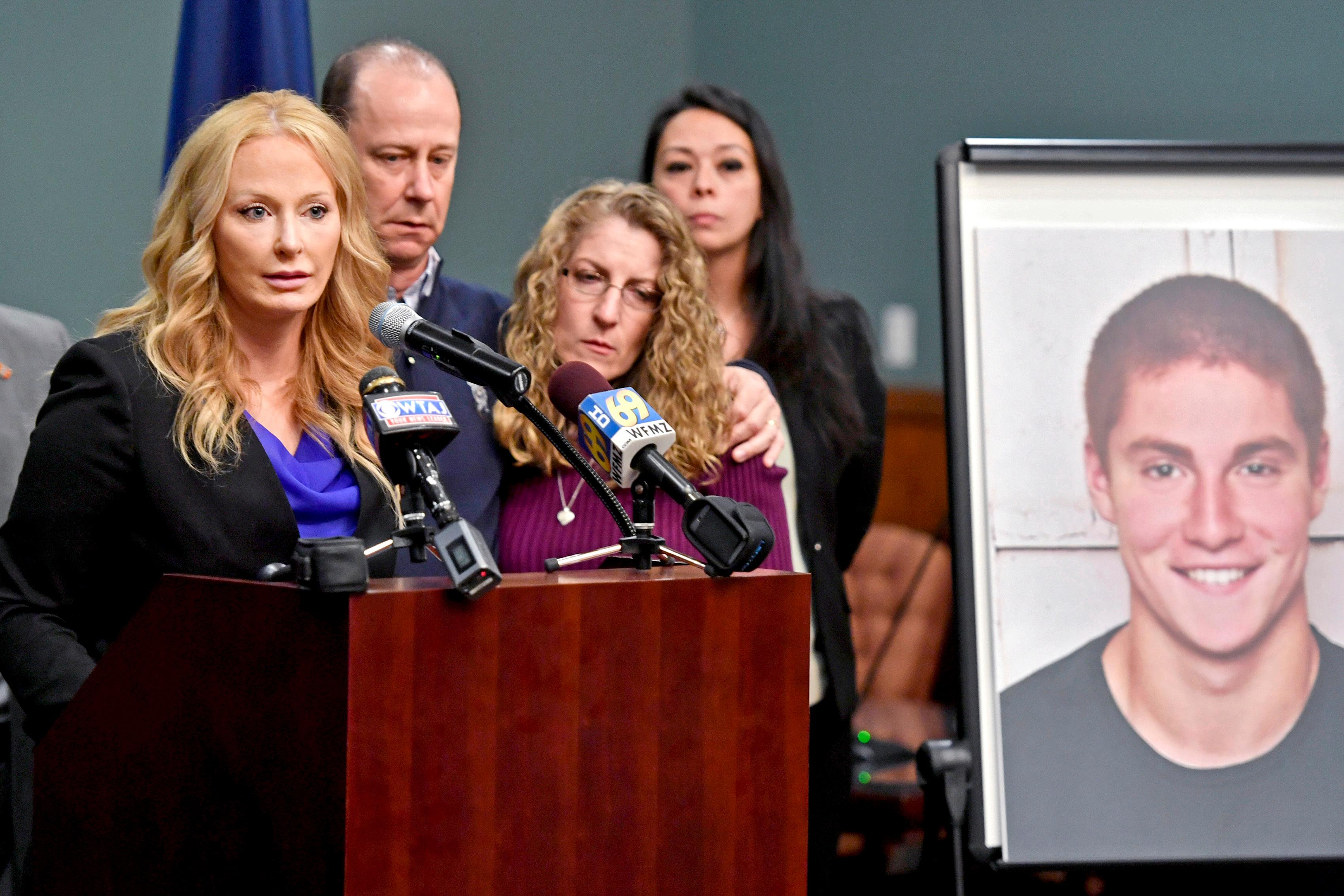 FILE – In this May 5, 2017, file photo, Centre County, Pa., District Attorney Stacy Parks Miller, left, announces findings an investigation into the death of Penn State University fraternity pledge Tim Piazza, seen in photo at right, as his parents, Jim and Evelyn Piazza, second and third from left, stand nearby during a news conference in Bellefonte, Pa. Parks Miller announced Monday, Nov. 13, 2017, that more charges have been filed against fraternity brothers after investigators recovered deleted surveillance video footage recorded before the Feb. 4, 2017, death of Piazza, of Lebanon, N.J., after a night of heavy drinking. (Abby Drey/Centre Daily Times via AP, File)/Centre Daily Times via AP)